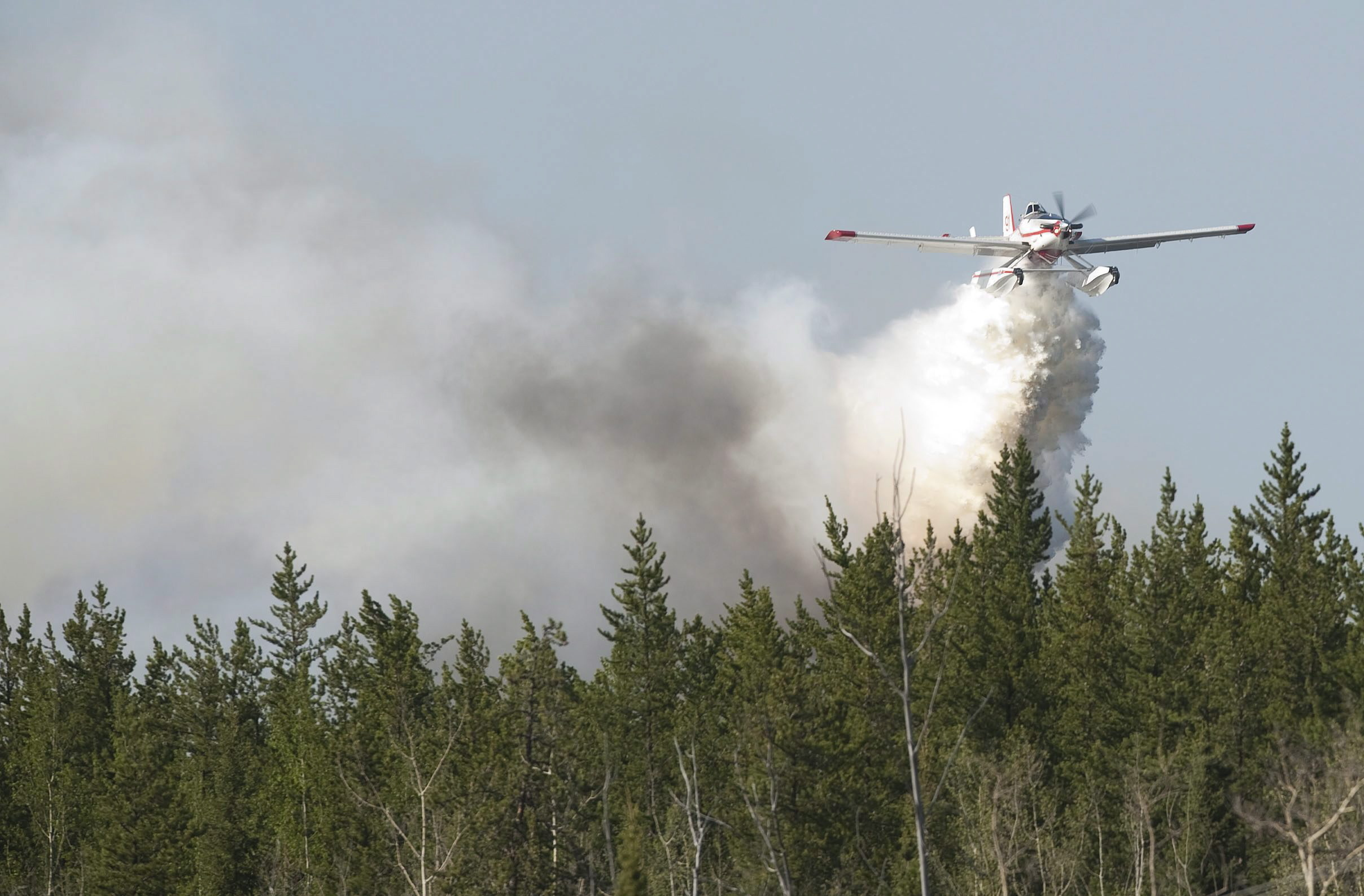 A water bomber drops its water on afire near Slave Lake, Alta. on May 15, 2011. More than 1,000 people were ordered to leave their homes when strong winds fanned two separate wildfires that burned on either side of the northern Alberta town. (Ian Jackson/The Canadian Press)