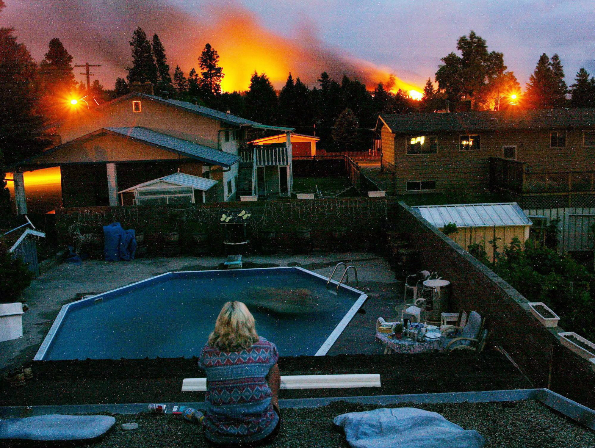 A resident watches the approaching flames in Kelowna on Aug. 22, 2003. More than 2,400 wildfires ravaged B.C. that summer. (THE CANADIAN PRESS/Rich Lam)