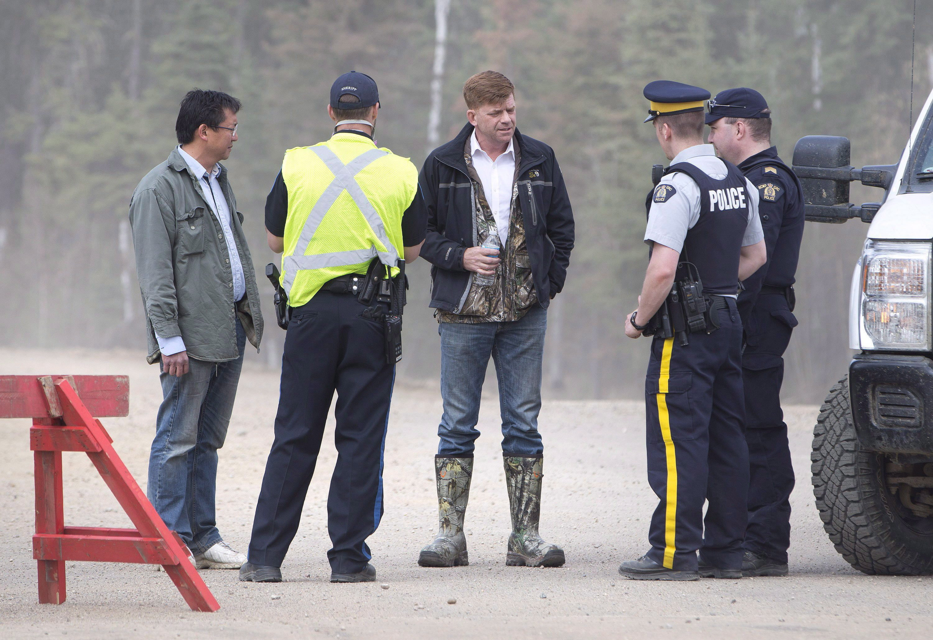 Brian Jean, centre, talks with police as the wildfire spread through the city, incinerating hundreds of properties on May 5, 2016. (Jason Franson/The Canadian Press)