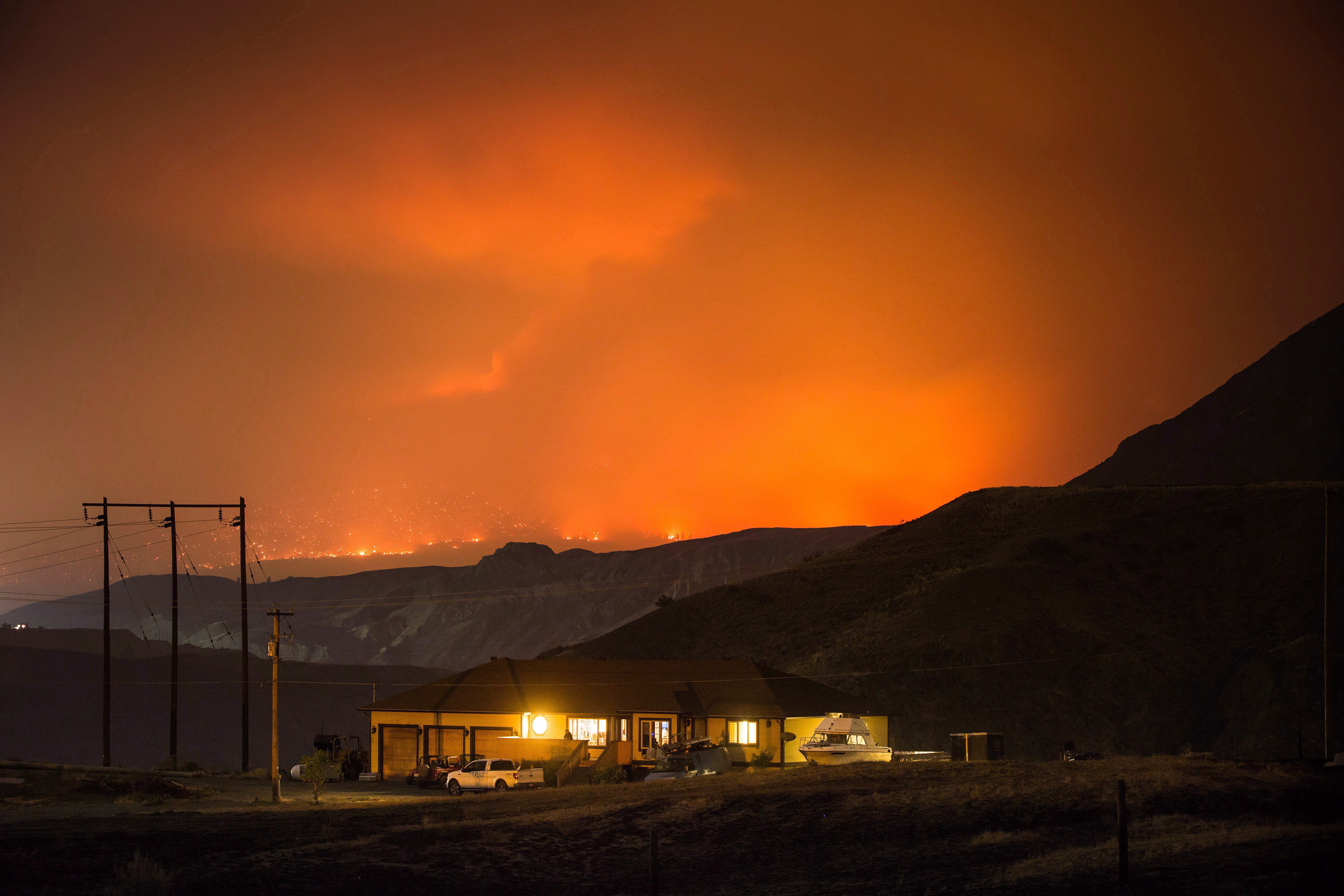 A wildfire burns on a mountain in the distance east of Cache Creek behind a house in Boston Flats, B.C., in the early morning hours of July 10, 2017. (Darryl Dyck/The Canadian Press)