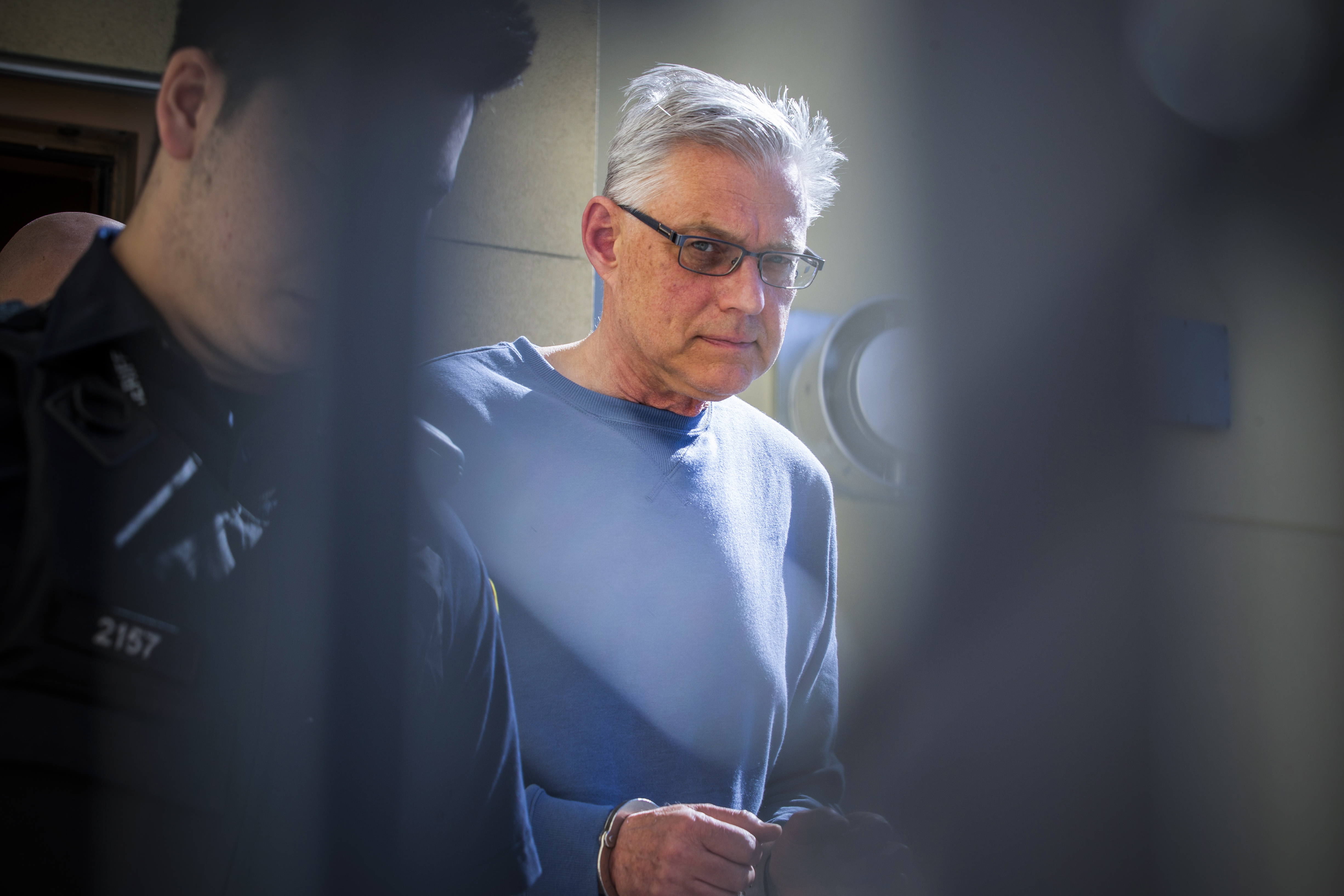 John Brittain, 68, is escorted in police custody at the Penticton Courthouse on April 16, 2019. Brittain was charged with three counts of first-degree murder and one count of second-degree murder in a Penticton shooting. (Ben Nelms/CBC)
