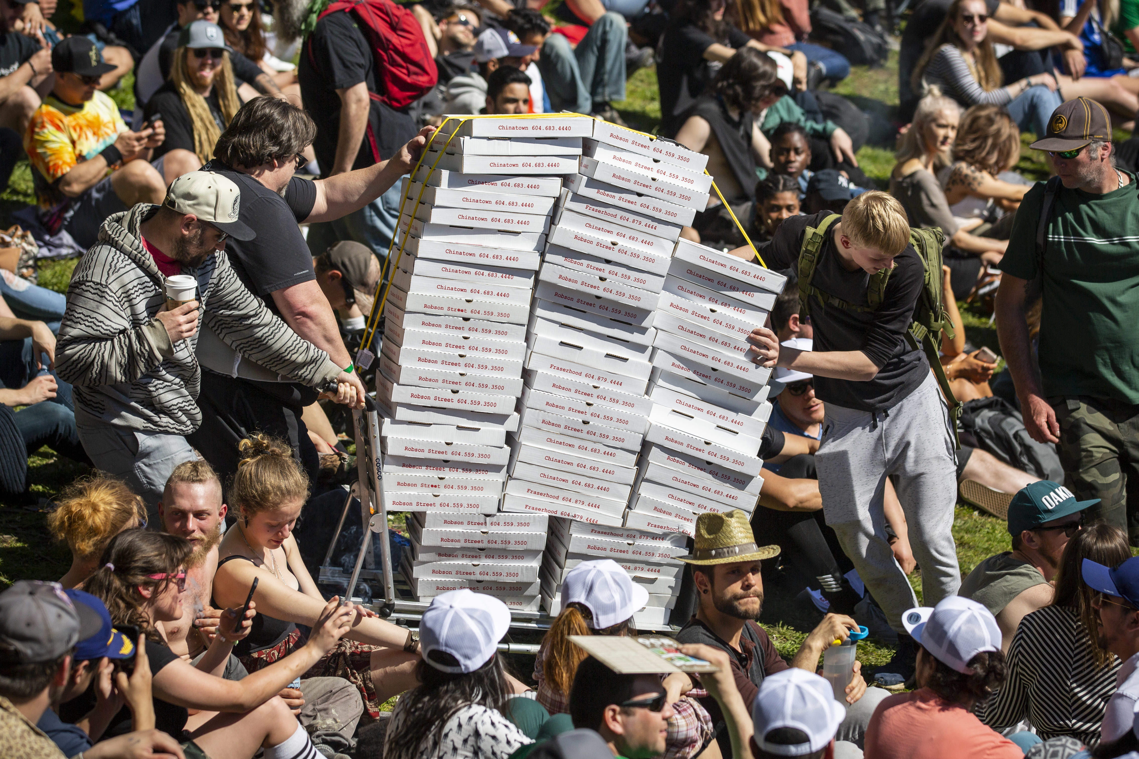 People push a cart of pizza during the annual 420 protest at Sunset Beach in Vancouver on Saturday, April 20, 2019. The 420 celebration — which organizers describe as a protest — features numerous cannabis vendors and a free concert by the hip hop group Cypress Hill. (Ben Nelms/CBC)