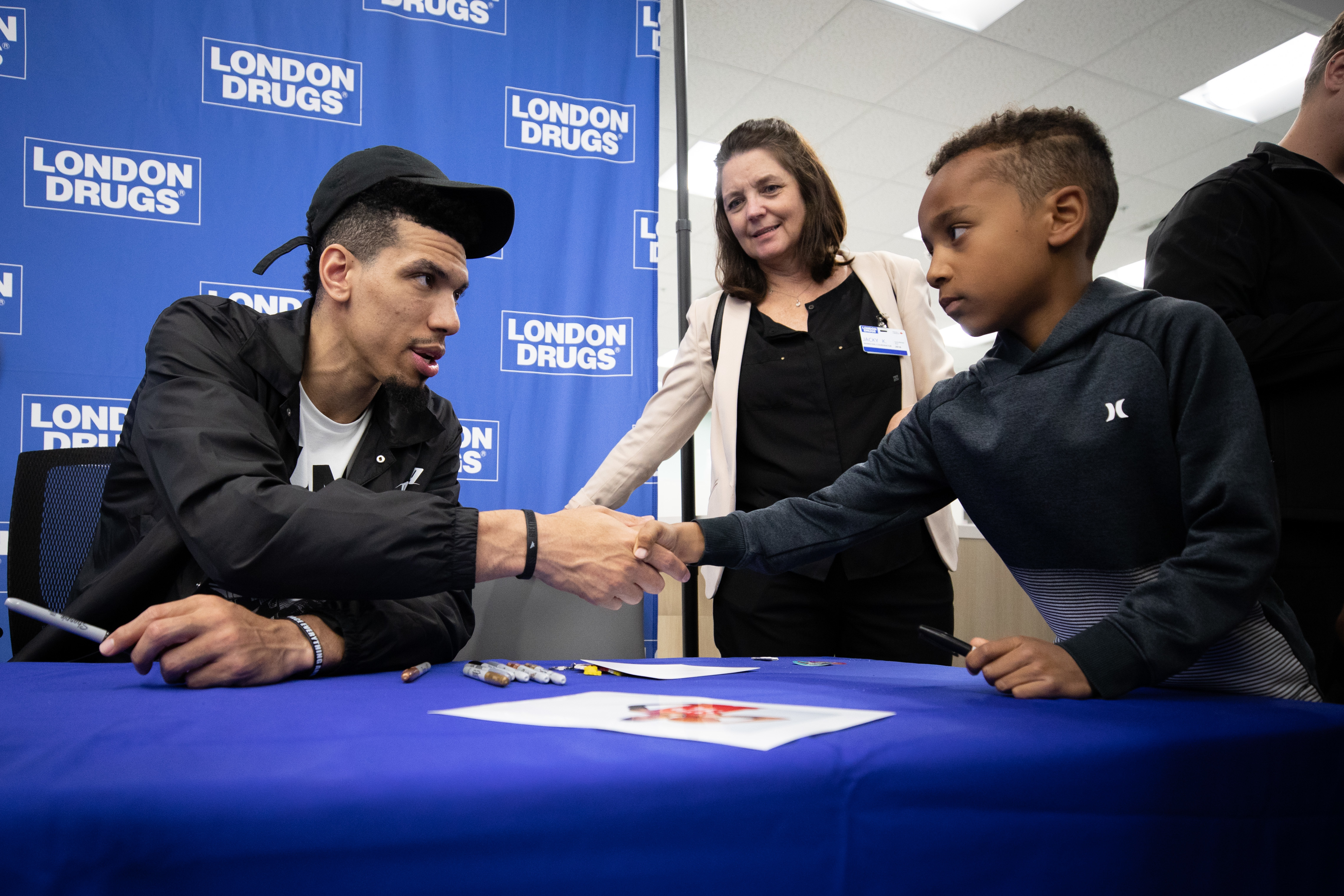Danny Green, former Toronto Raptors basketball player, shakes hands with a young fan at London Drugs in Vancouver on July 5, 2019. (Maggie MacPherson/CBC)