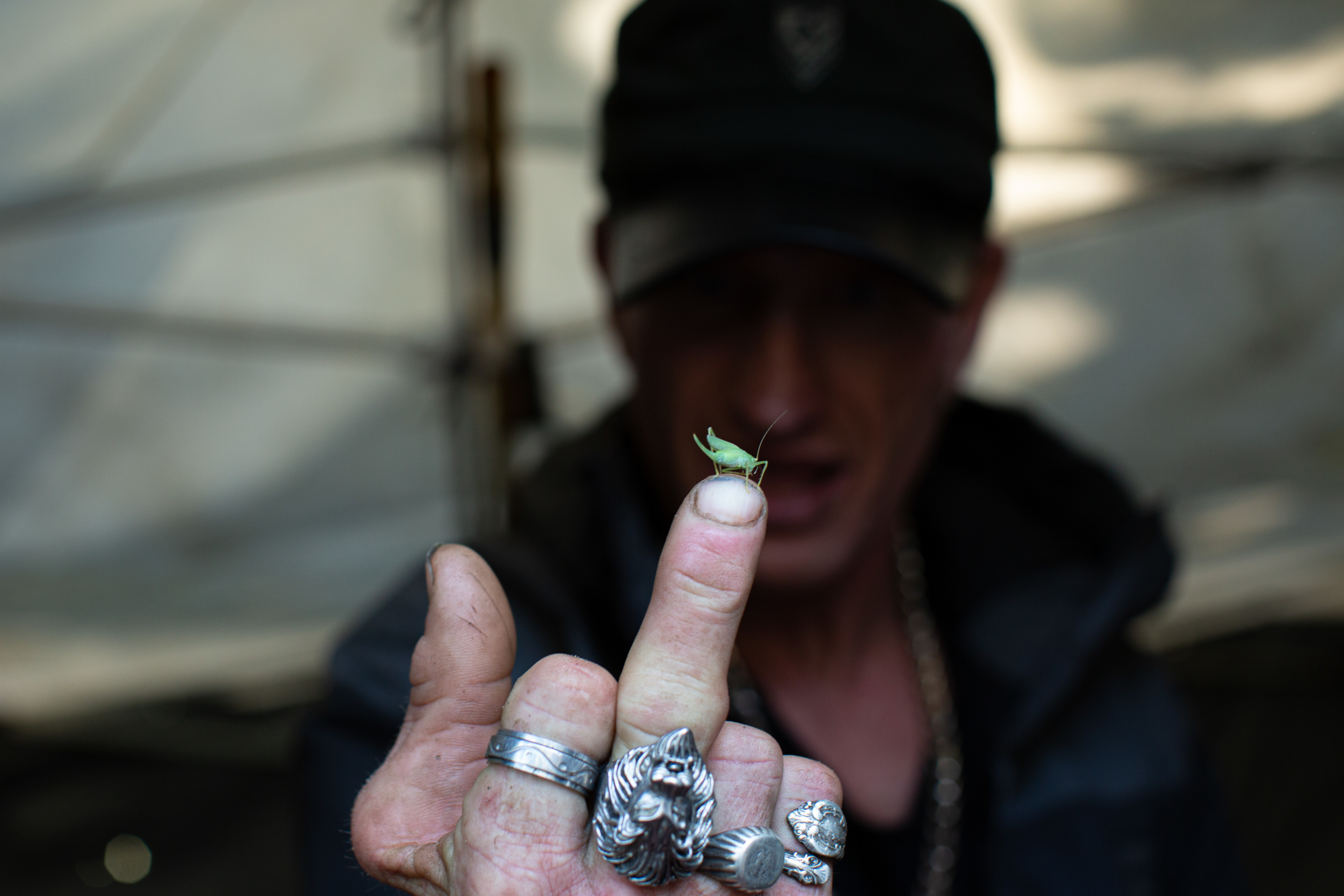 Oppenheimer Park resident Stephen James (Red) Robinson, 51, looks at a tiny grasshopper while flipping the bird in Vancouver on July 18, 2019. (Maggie MacPherson/CBC)