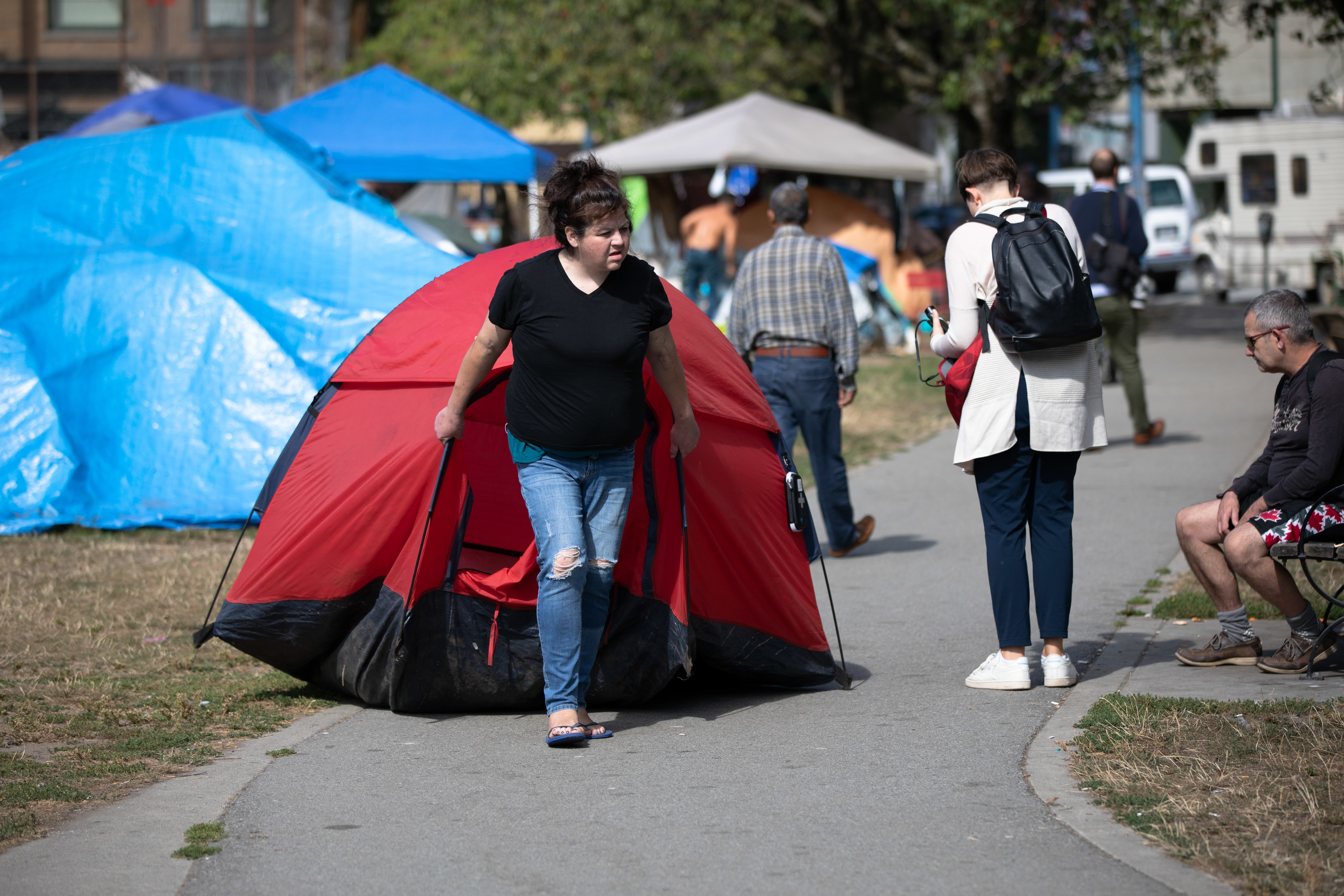 A woman drags her tent to a new area of the homeless camp in Vancouver's Oppenheimer Park on Aug. 19, 2019. (Maggie MacPherson/CBC)