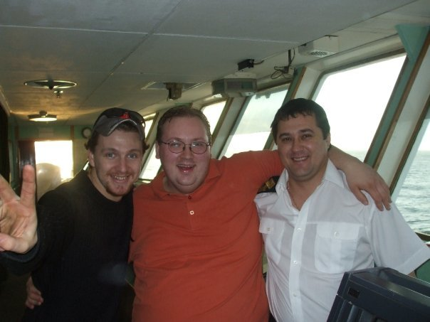 Jason Whittle, centre, poses on the bridge of the MV Lyubov Orlova with two Russian crew.