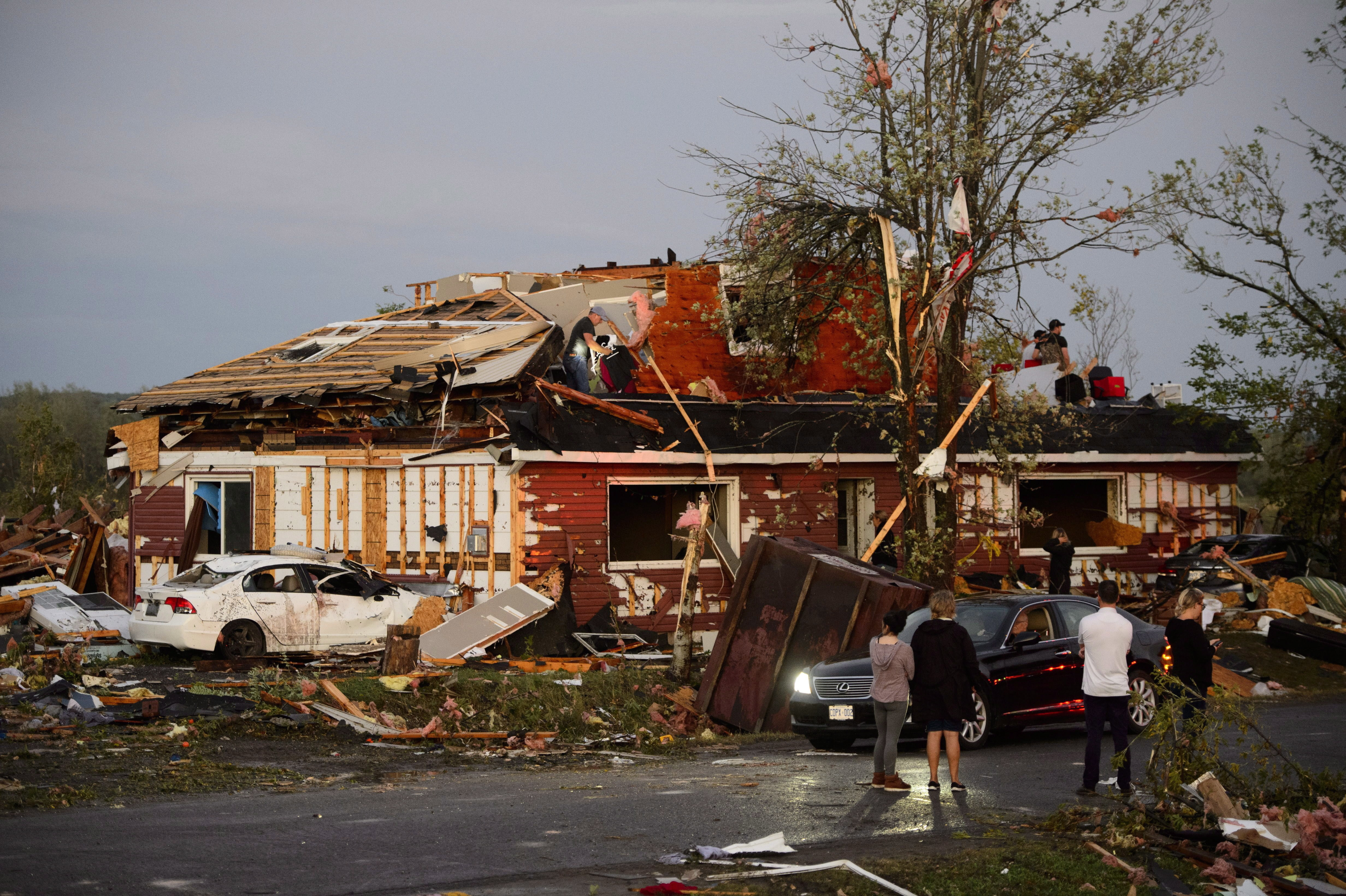 A group of people gather to inspect the damage caused by the tornado that hit Dunrobin. (Sean Kilpatrick/Canadian Press)