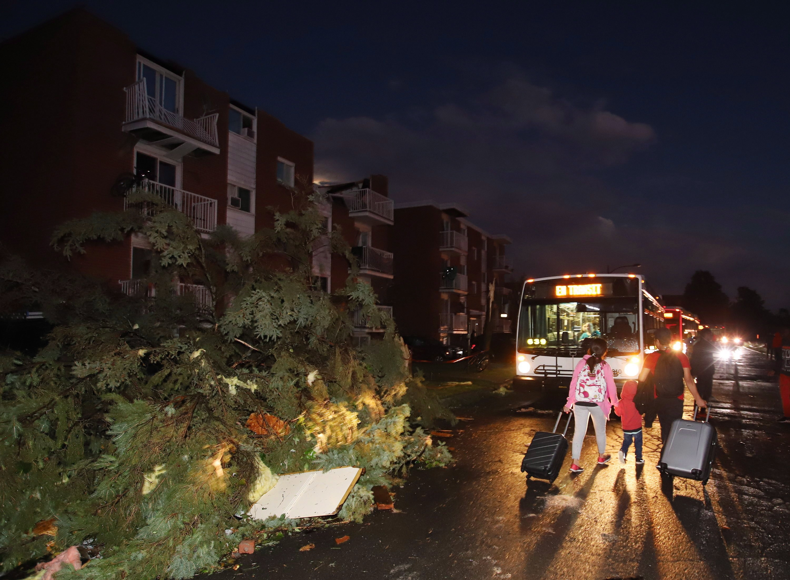 Residents board buses after the roofs of apartment buildings were torn off and windows were blown out in the Gatineau neighbourhood of Mont-Bleu. (Fred Chartrand/Canadian Press)