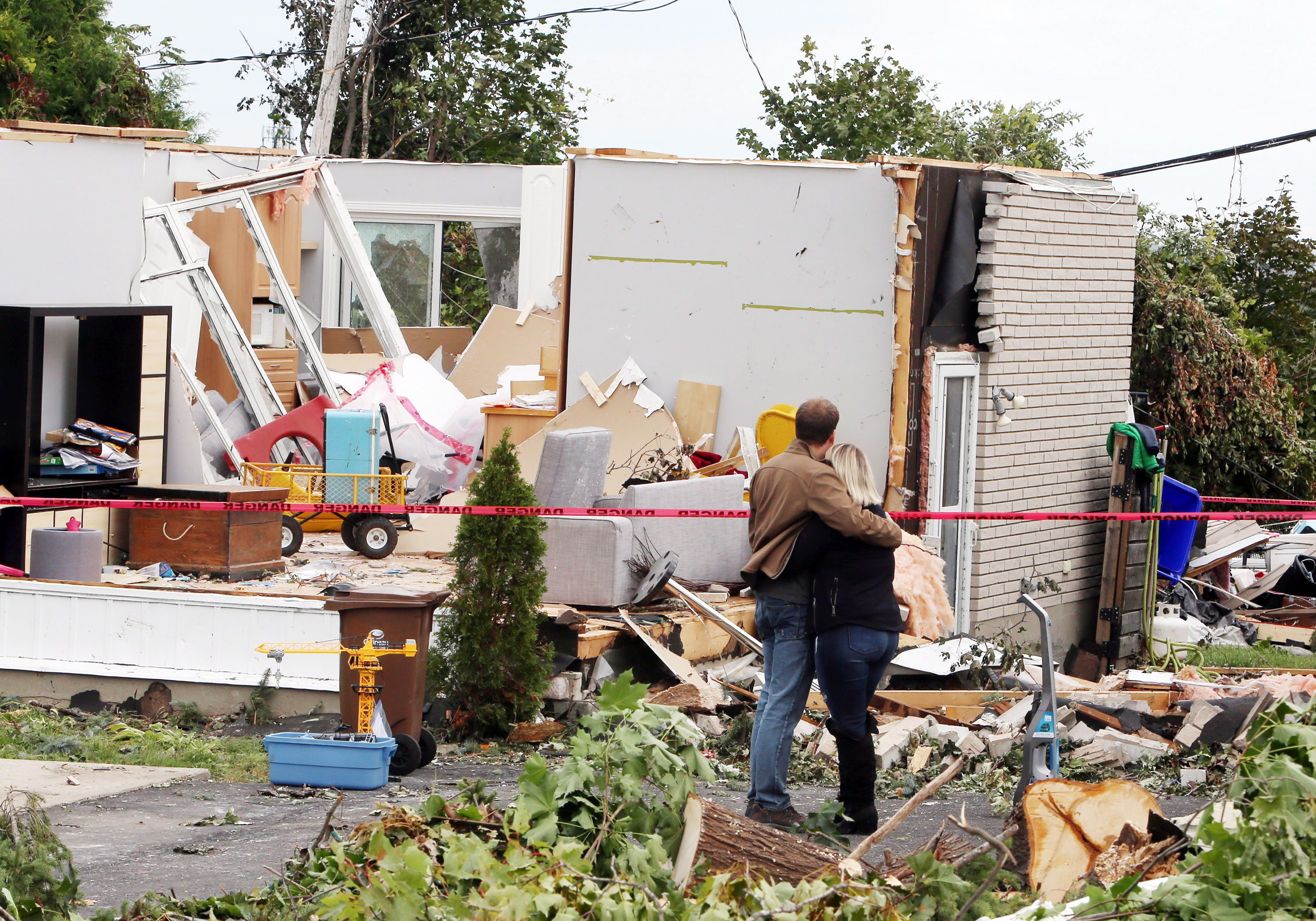 A man and woman embrace as they survey the damage to a home in Gatineau on Sept. 23. (Fred Chartrand/Canadian Press)