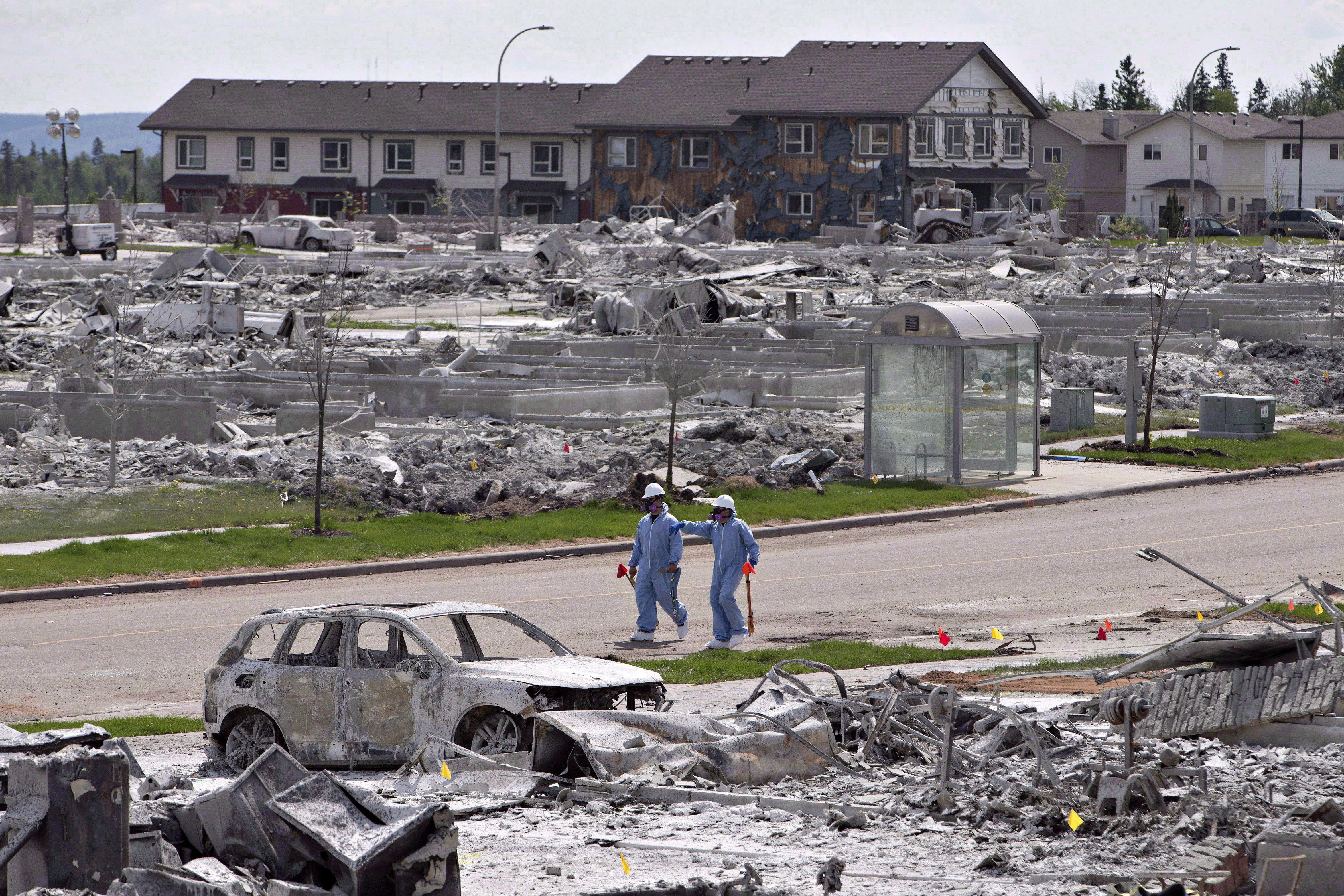 Workers put out markers around a devastated area of Timberlea in Fort McMurray Alta., on June 2, 2016. (Jason Franson/The Canadian Press)