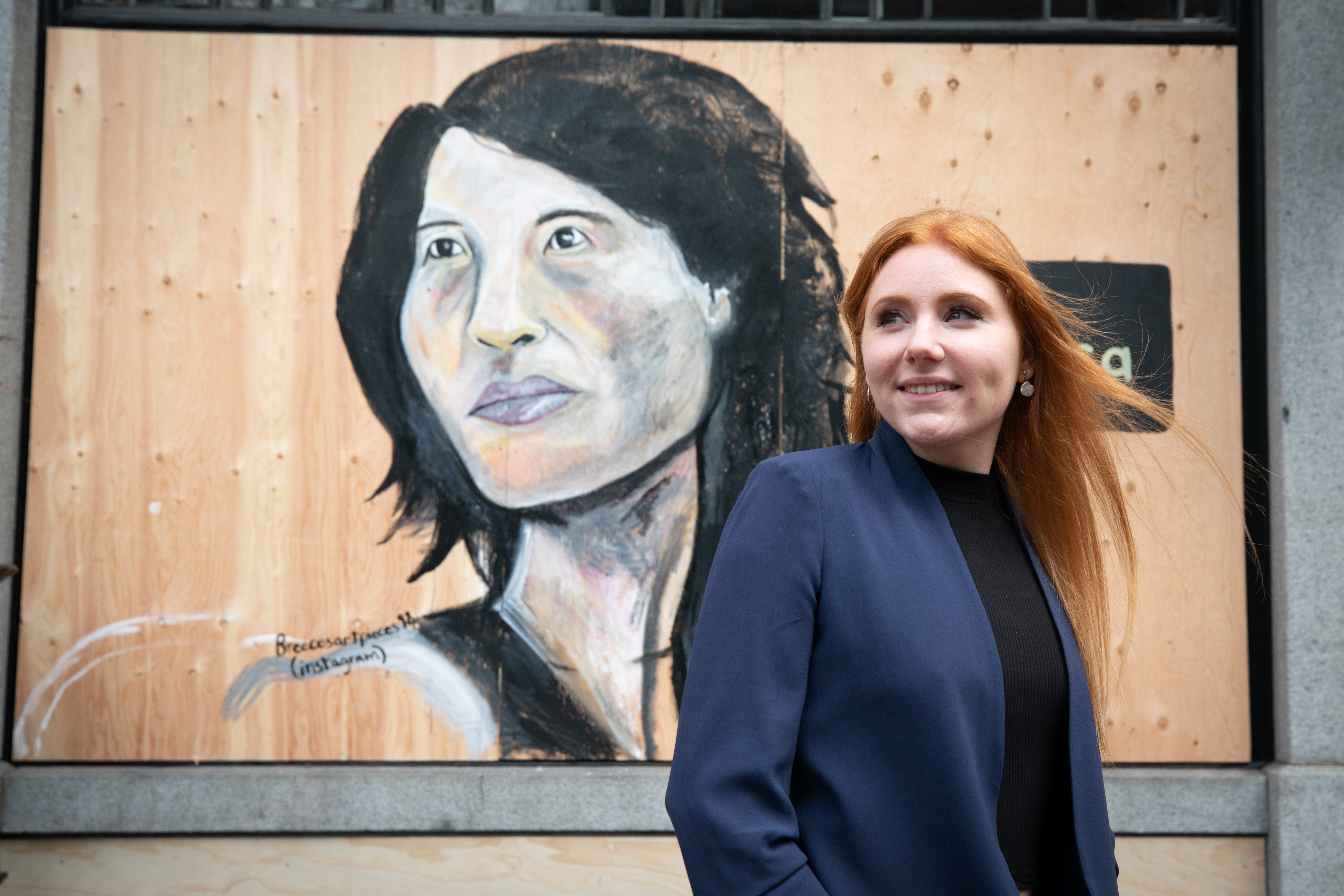 Artist Breece Austin stands in front of a mural she painted of Canada's chief public health officer Dr. Theresa Tam.
