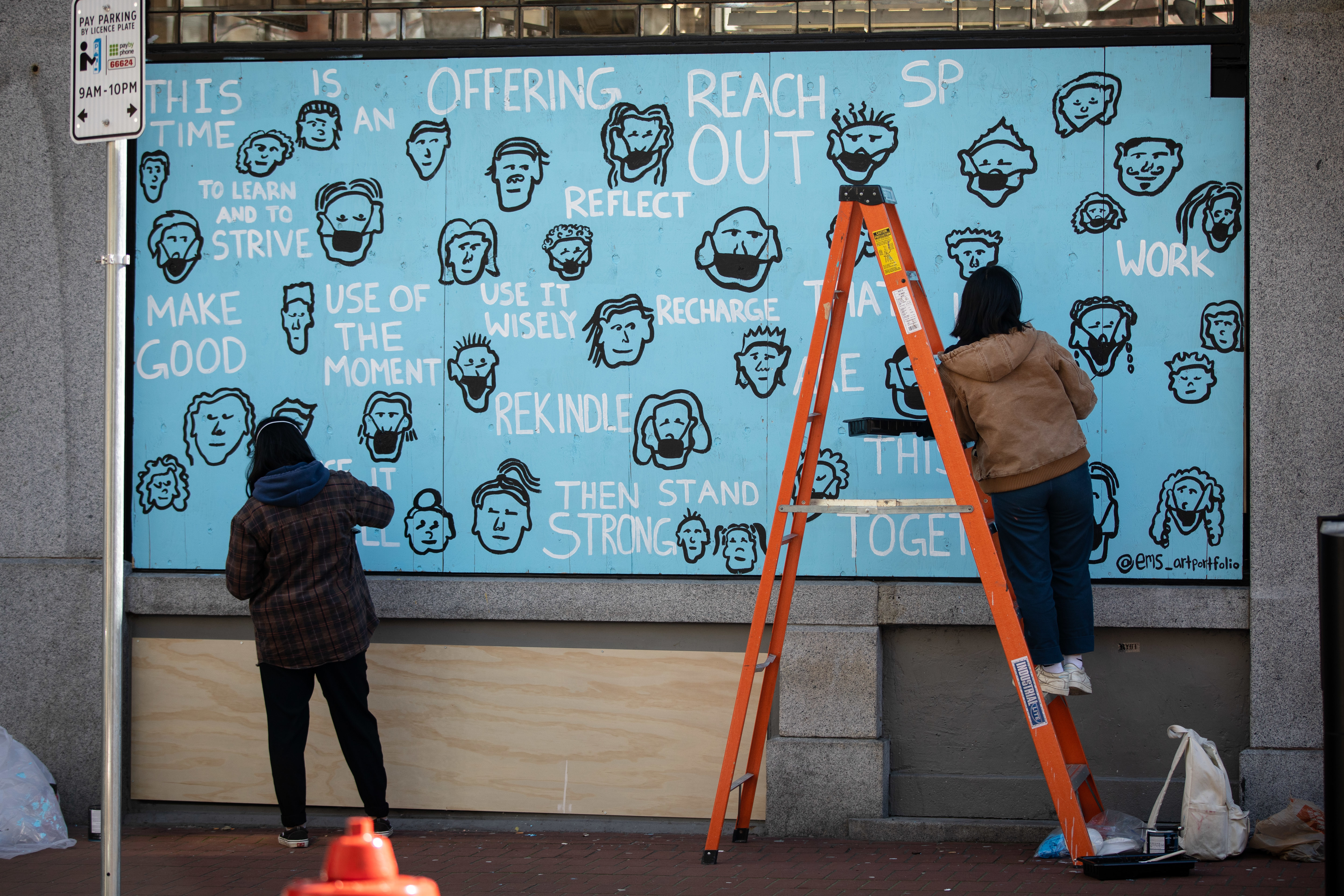 Artist Emerald Repard-Denniston paints a mural with help from her sister Bella. The words are taken from a poem her mother wrote about the pandemic.