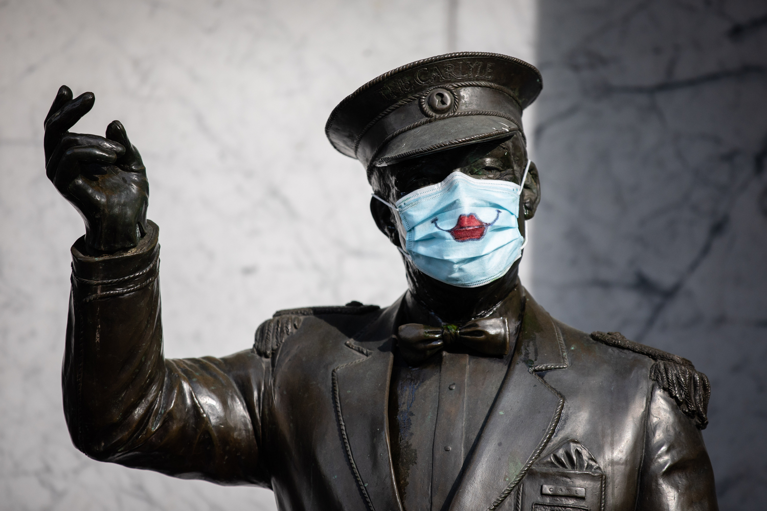 Statue wearing a mask with smiling painted lips is pictured outside of Carlyle Apartments in Vancouver on April 27, 2020. (Maggie MacPherson/CBC)