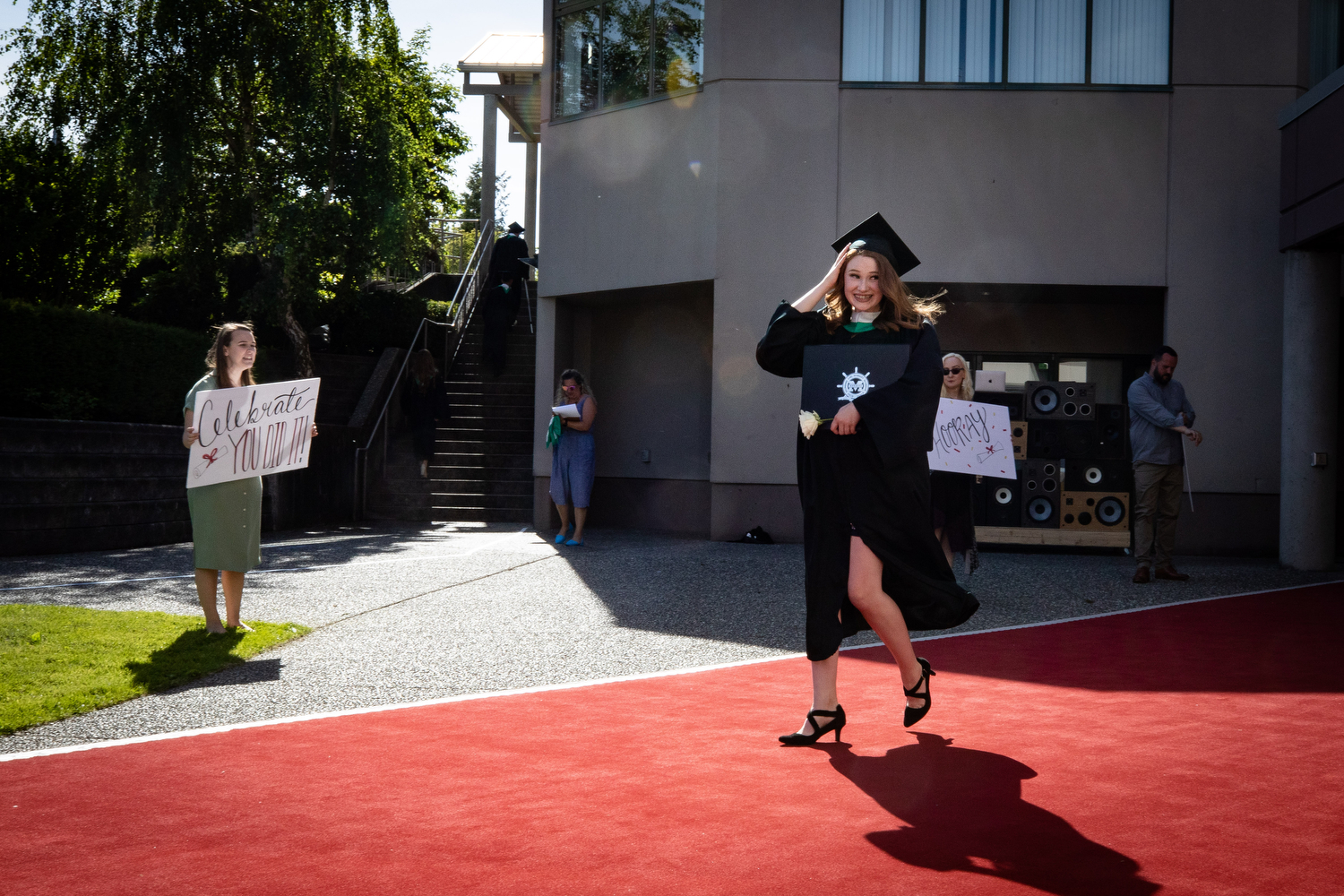An Earl Marriott Secondary School graduate walks down a red carpet at a physically distanced graduation ceremony in Surrey on May 27, 2020. (Maggie MacPherson/CBC)
