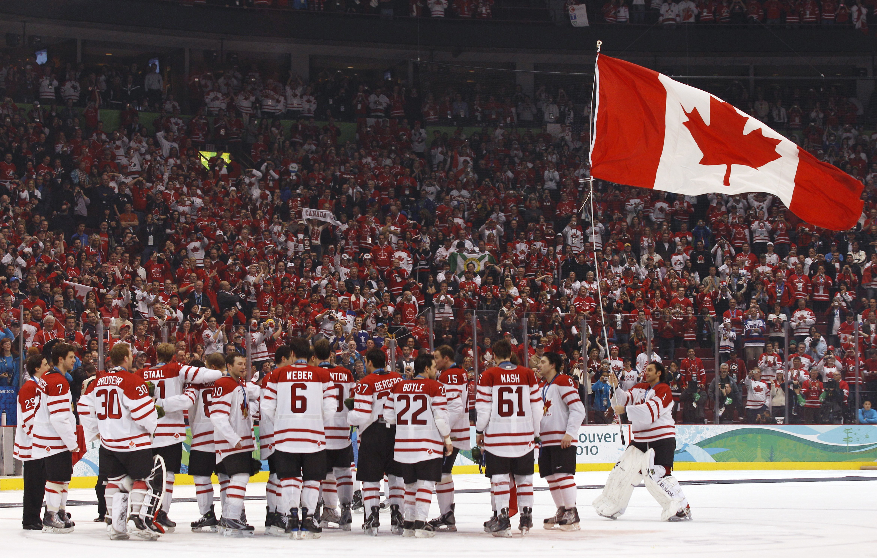 Team Canada goalie Roberto Luongo, right, skates with the Canadian flag after defeating the U.S. in the gold medal hockey game at the Vancouver 2010 Winter Olympics, Feb. 28, 2010. (Hans Deryk/Reuters)