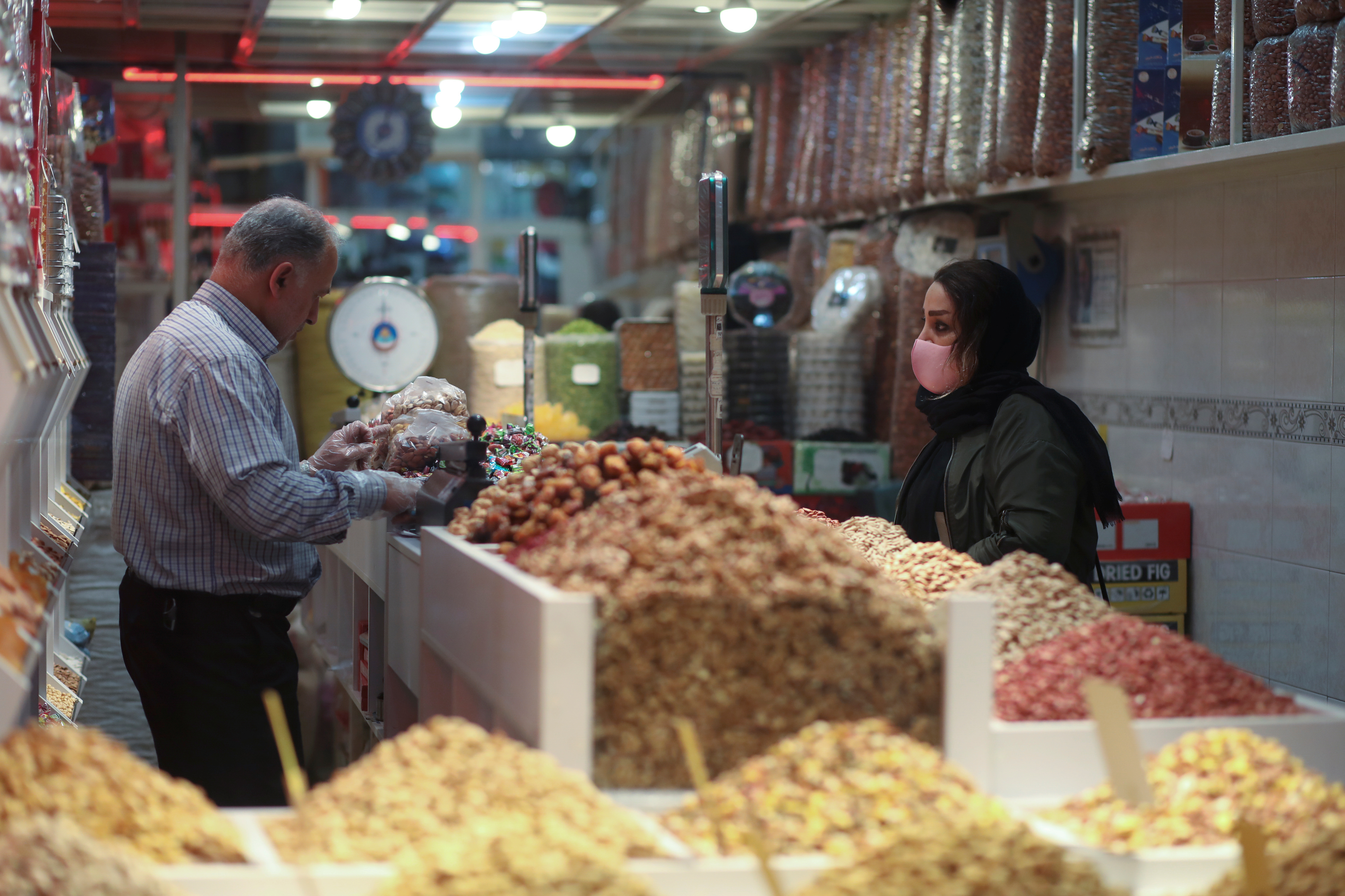 A woman wears a protective face mask during the COVID-19 pandemic as she shops at Tajrish Bazar in Tehran ahead of Nowruz in March 2021. (Ali Khara/West Asia News Agency/Reuters)