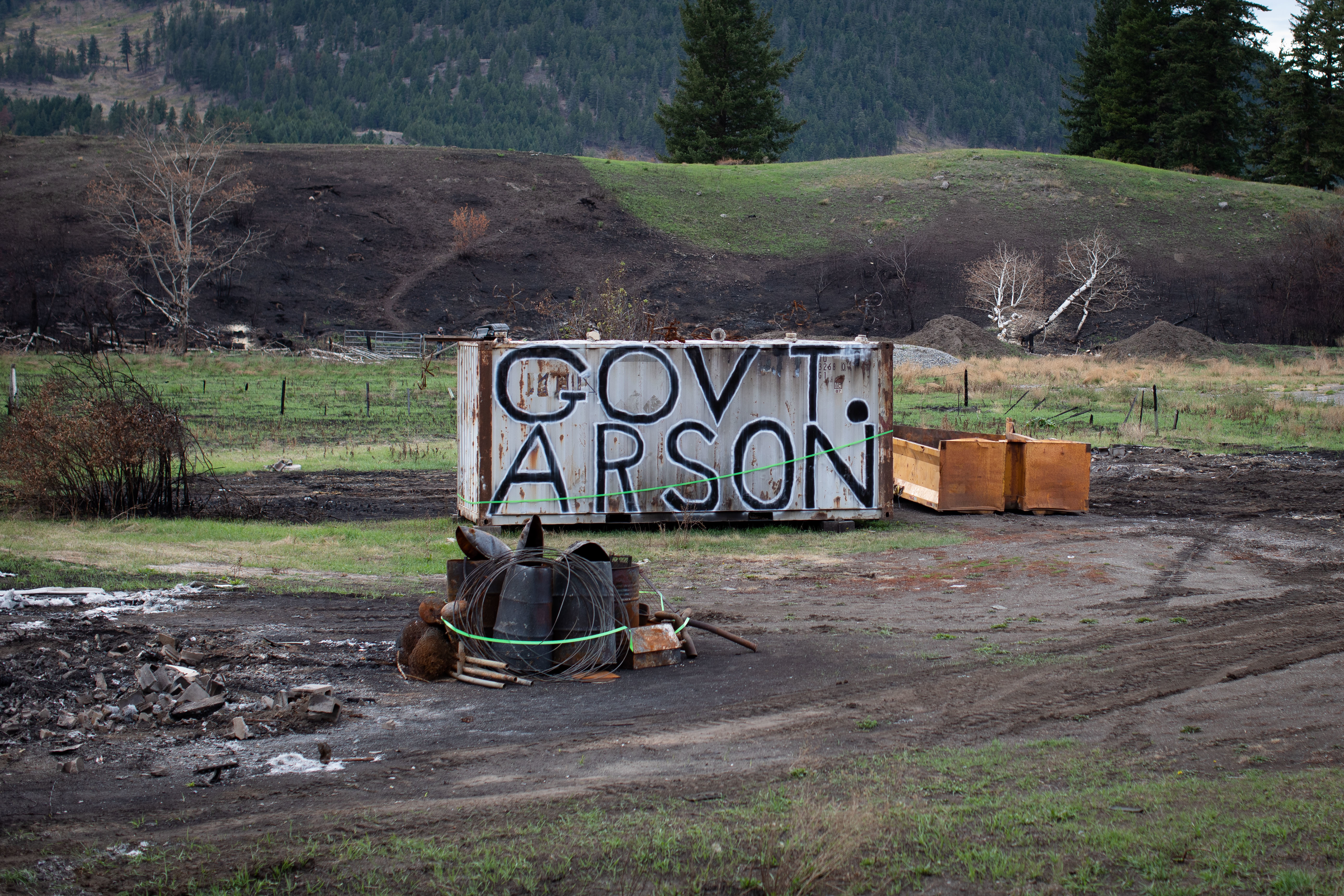 An anti-government message is written on the side of a shipping container near the remnants of a burned-down trailer home in Monte Lake, B.C., on Sept. 1. (Maggie MacPherson/CBC)