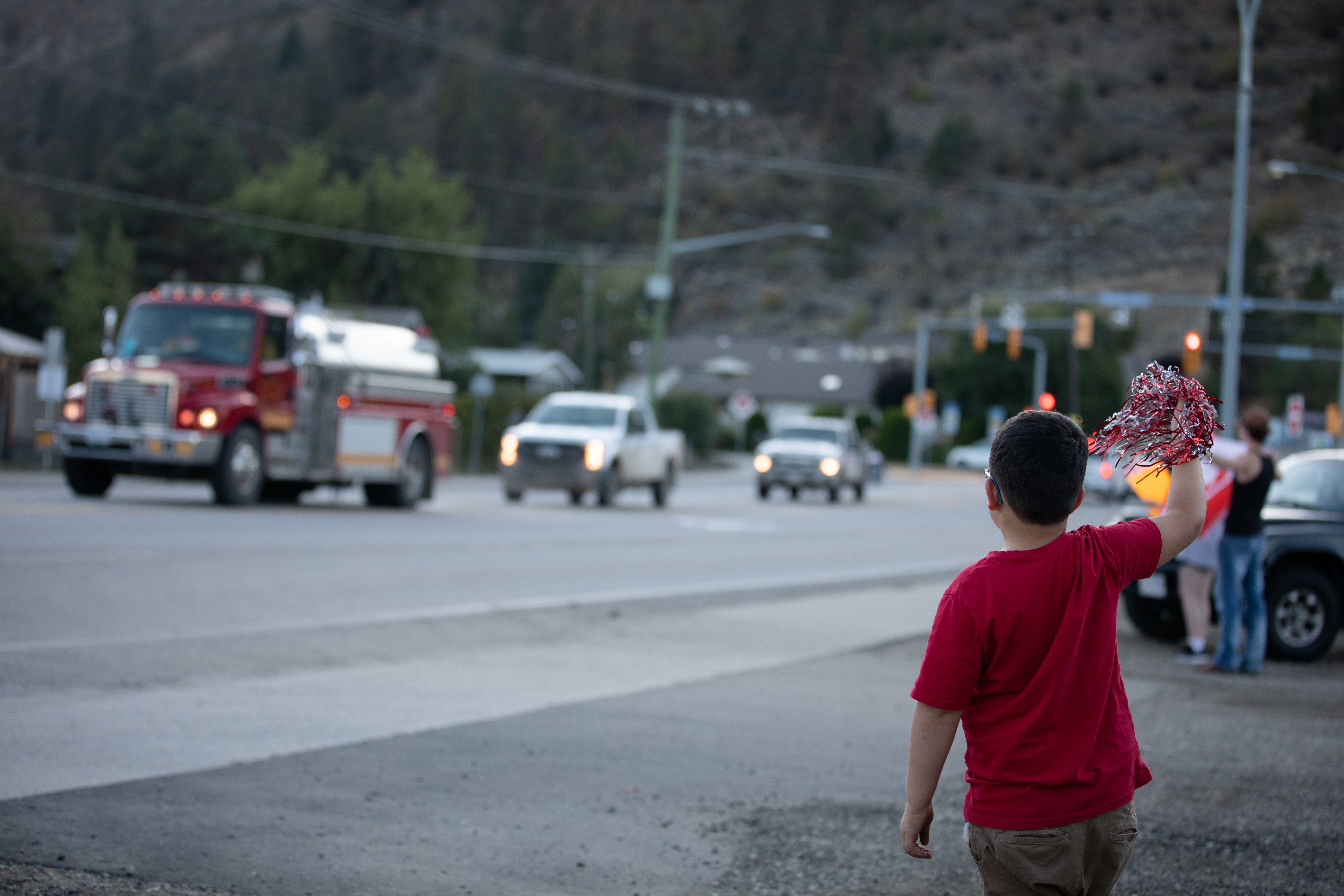 A young boy cheers firefighters as they return from their shifts in Vernon, B.C., on Sept. 2. (Maggie MacPherson/CBC)
