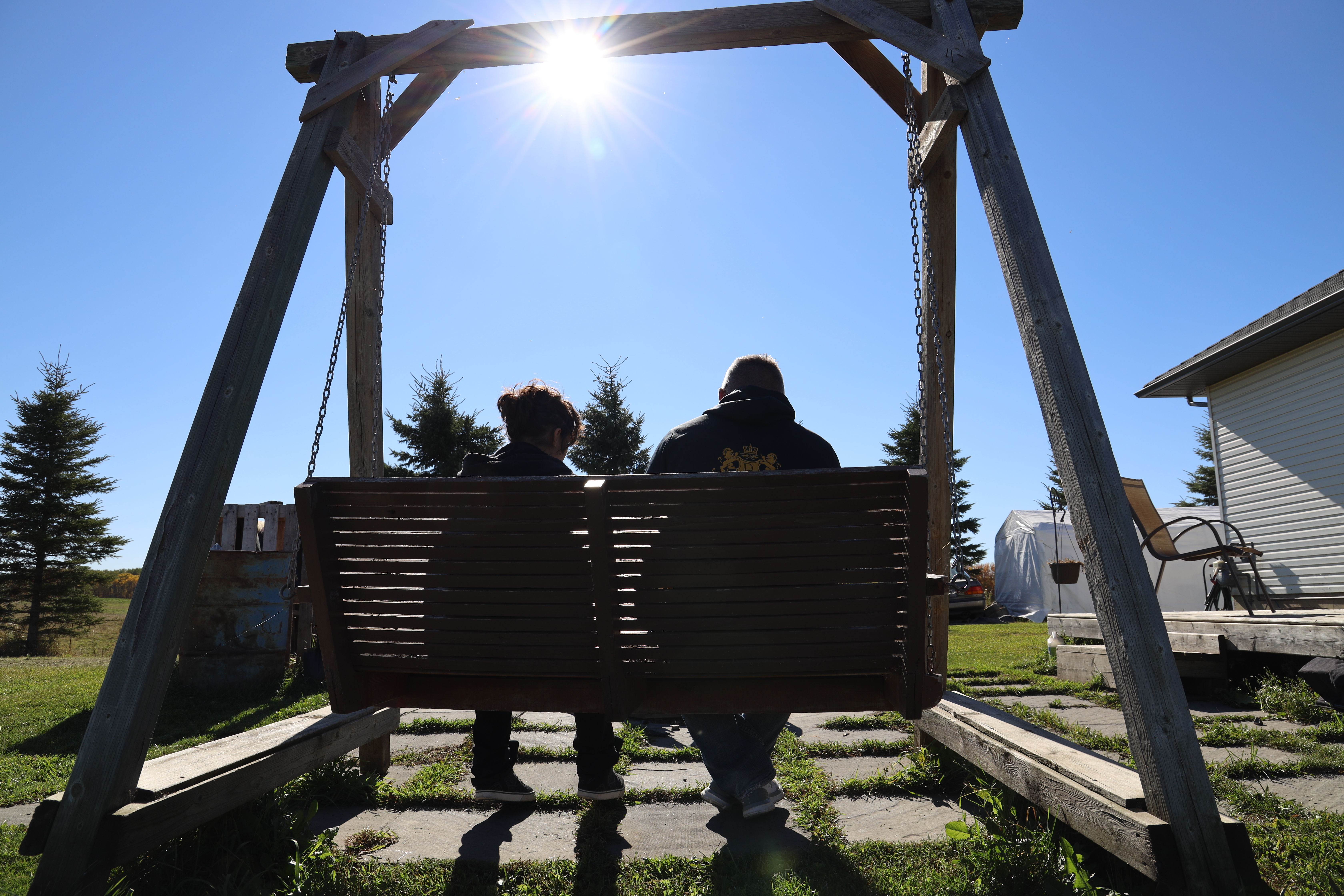 One of the alleged victims of Dominey sits with his fiancé on a rural property in Alberta. (Sam Martin/CBC)