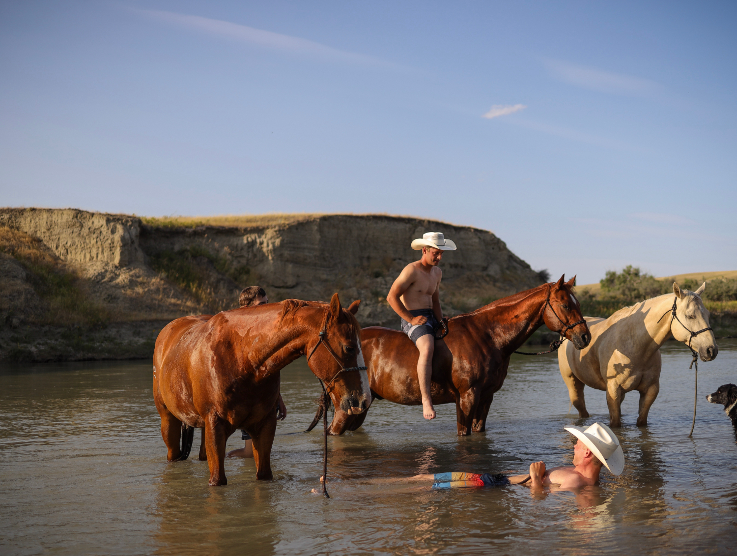 Ben Bamford, left, and Tate Mosby cool off in the Milk River before the start the rodeo.