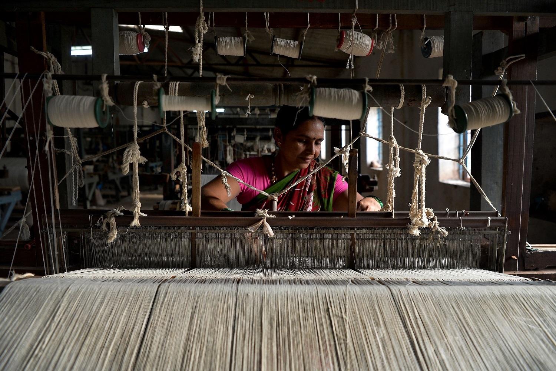 This photo taken on May 9, 2018 shows an employee of Khadi Gramodyog Samyukta Sangh weaving cotton yarn at Tulasigeri village in the southern Indian state of Karnataka. (Manjunath Kiran/AFP/Getty Images)