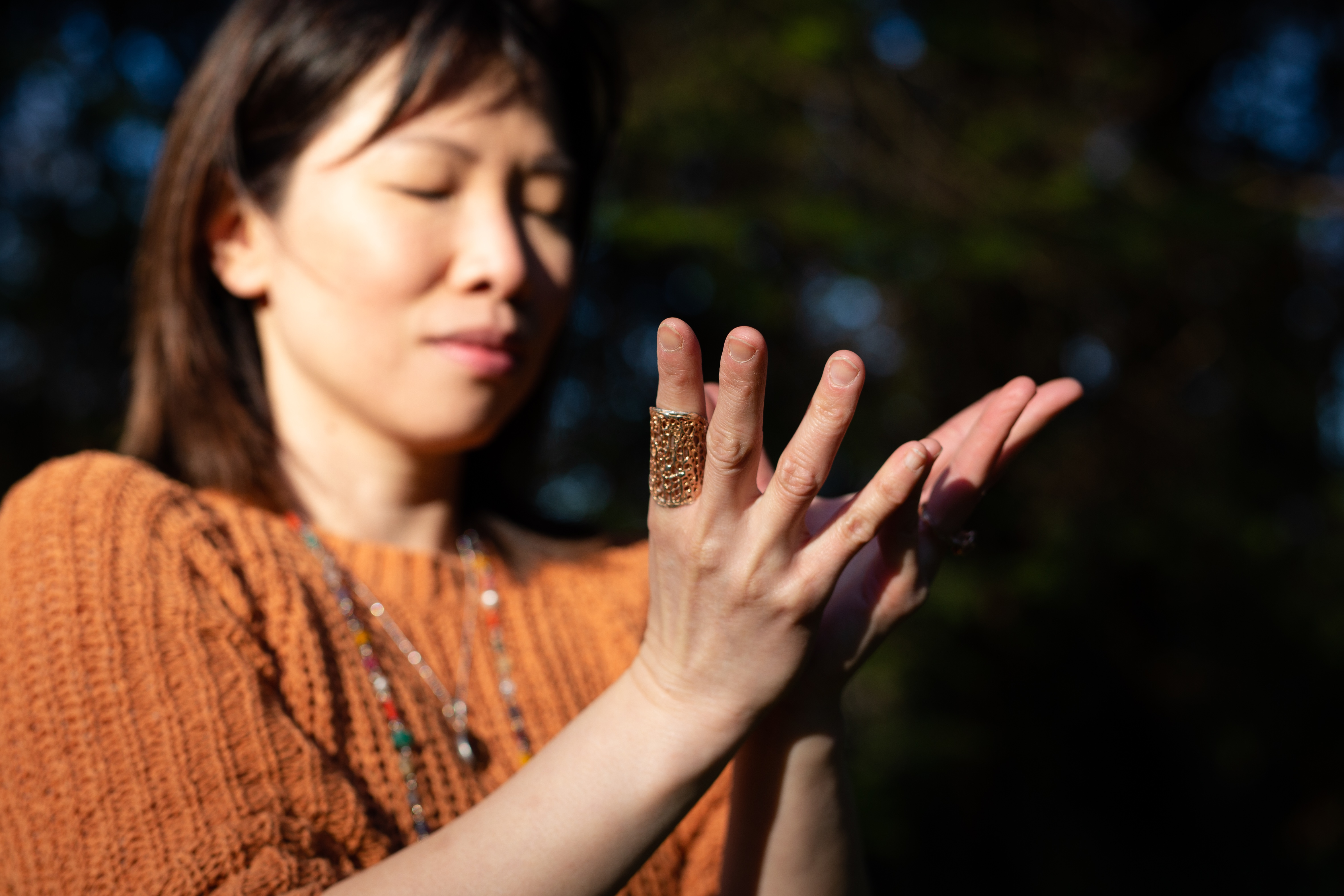 Yoga therapist Zoe Ho puts her hands in lotus mudra, a hand gesture symbolizing light and beauty emerging from the darkness.