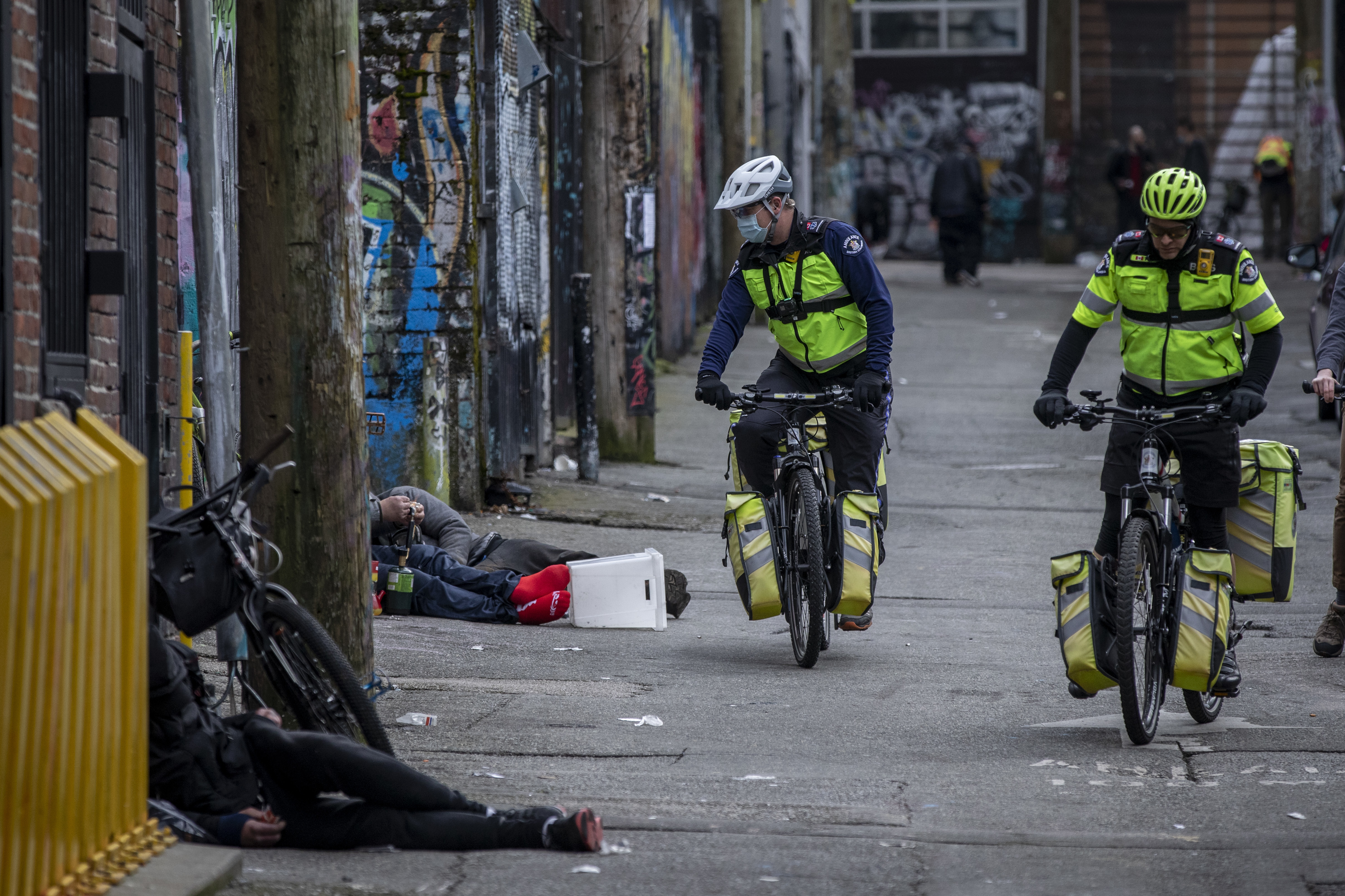 "Rodney Siudut, left, and Tom Venables ride through an alley in the Downtown Eastside. The bike paramedics not only respond to calls from emergency dispatchers but also ""self-generate"" calls on their own from what they see on their patrols. (Ben Nelms/CBC)"
