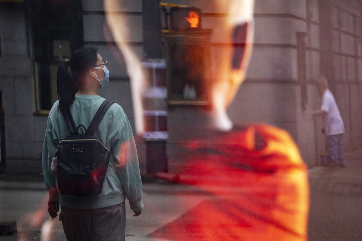 A woman wearing a surgical mask is pictured in a reflection from an advertisement in downtown Vancouver on Aug. 6, 2020. (Ben Nelms/CBC Vancouver)