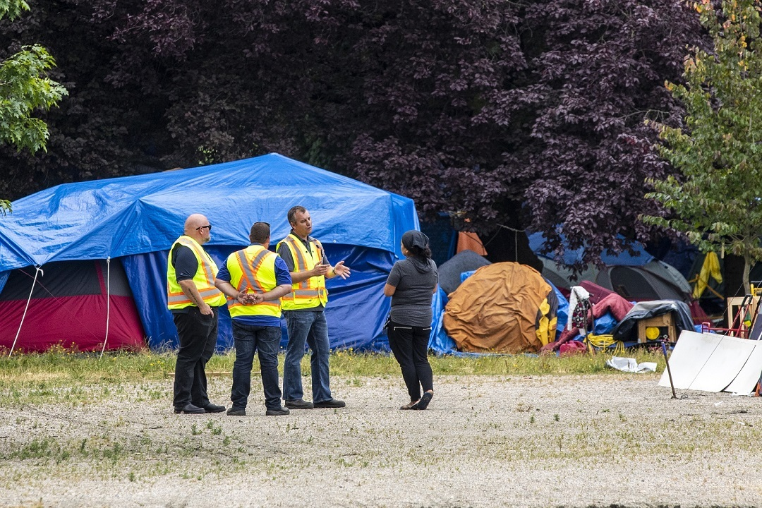 City of Vancouver workers speak with camp liasion Chrissie Brett in August. Since summer, Vancouver police say the number of calls for service at the park have increased. (Ben Nelms)