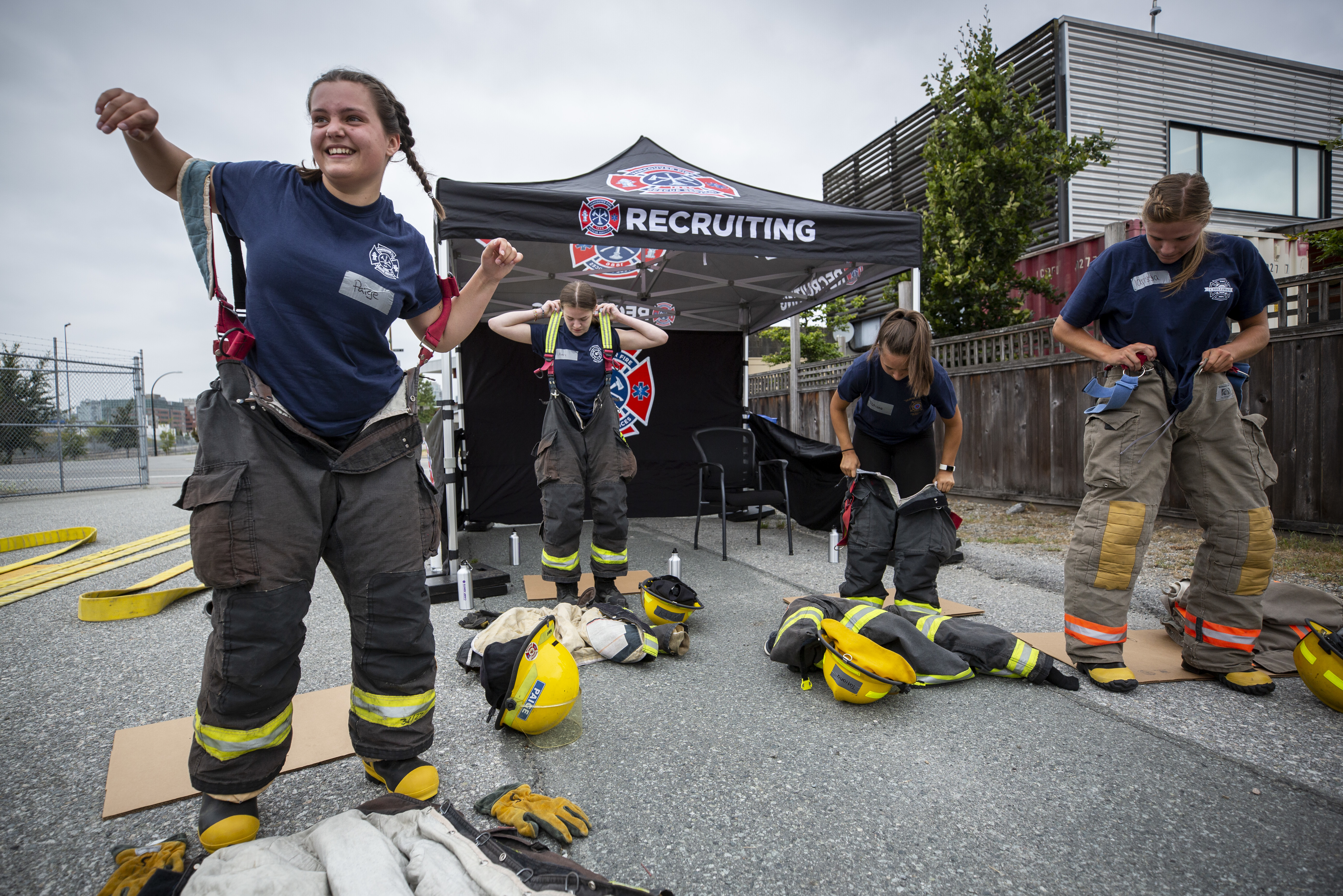 Girls at Camp Ignite put on their firefighting equipment before a training exercise. The gear is heavy, and most of them have never put it on before. (Ben Nelms/CBC)