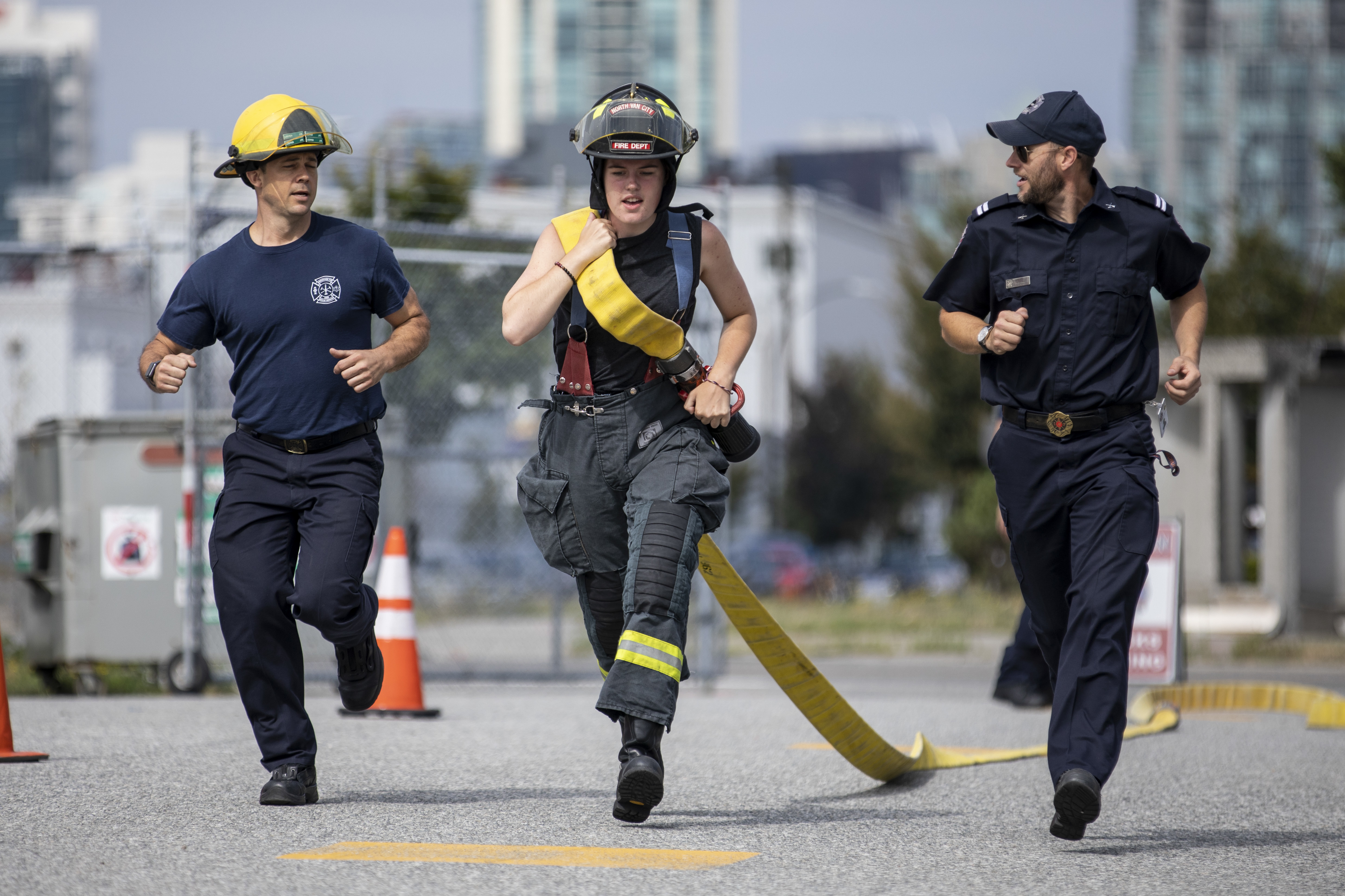 A Camp Ignite participant runs with a firehose as part of a training exercise for endurance and strength. (Ben Nelms/CBC)