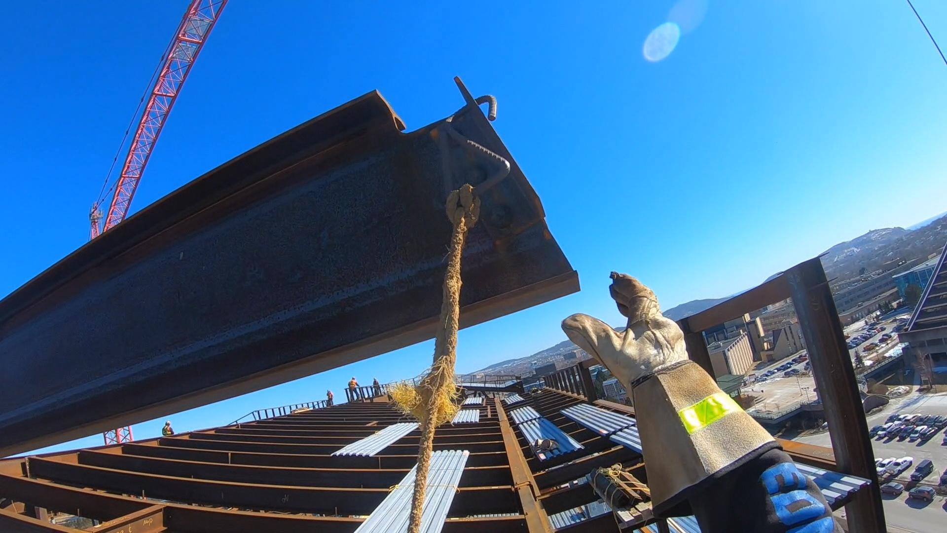 Gene Lewis reaches out to grab a steel beam. (CBC)