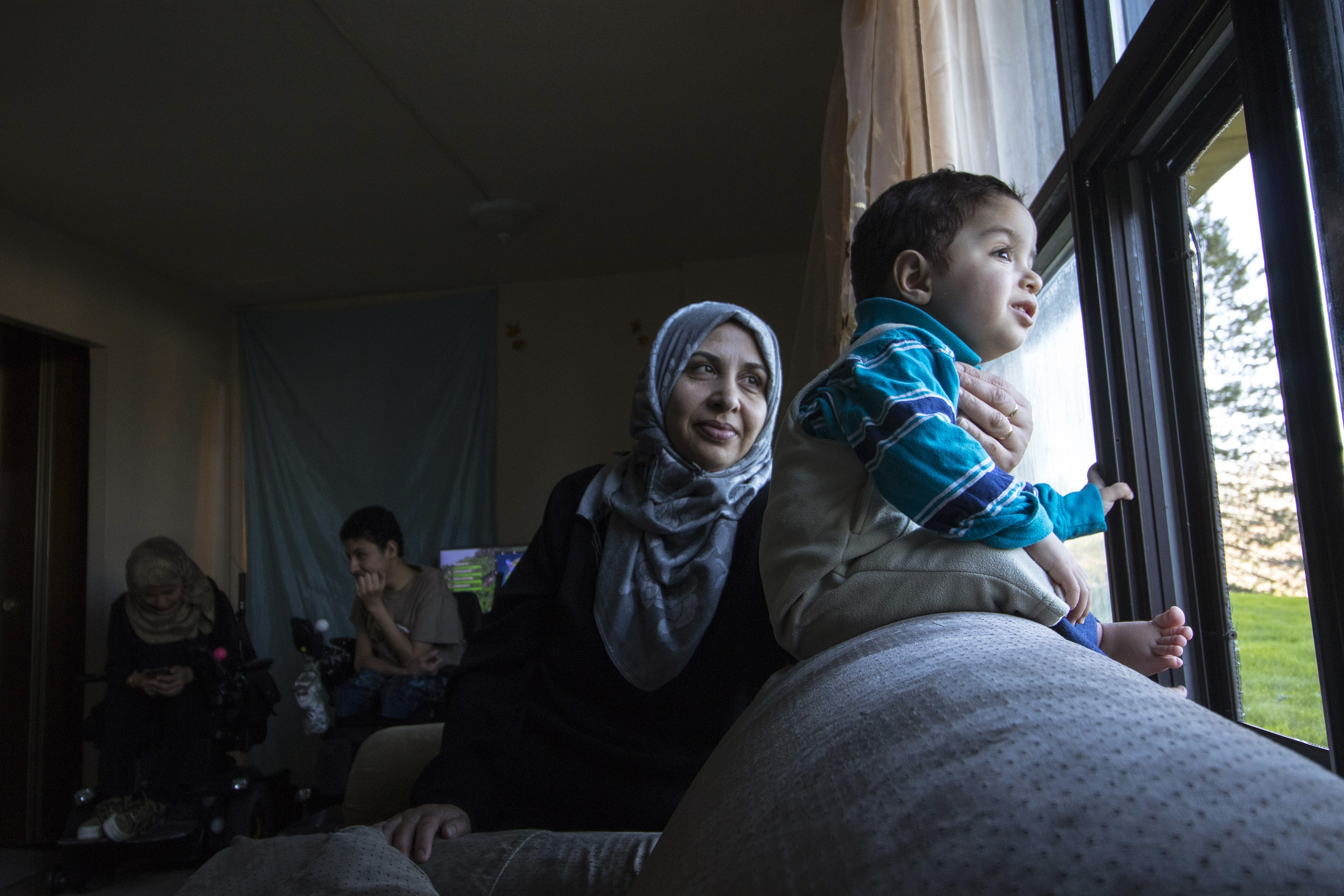 Eighteen-month-old Mias looks out the window of the family's apartment as his mother, Jawaher Aljanadi, looks on. Maher and Marwa are in the background. (Dave Irish/CBC)