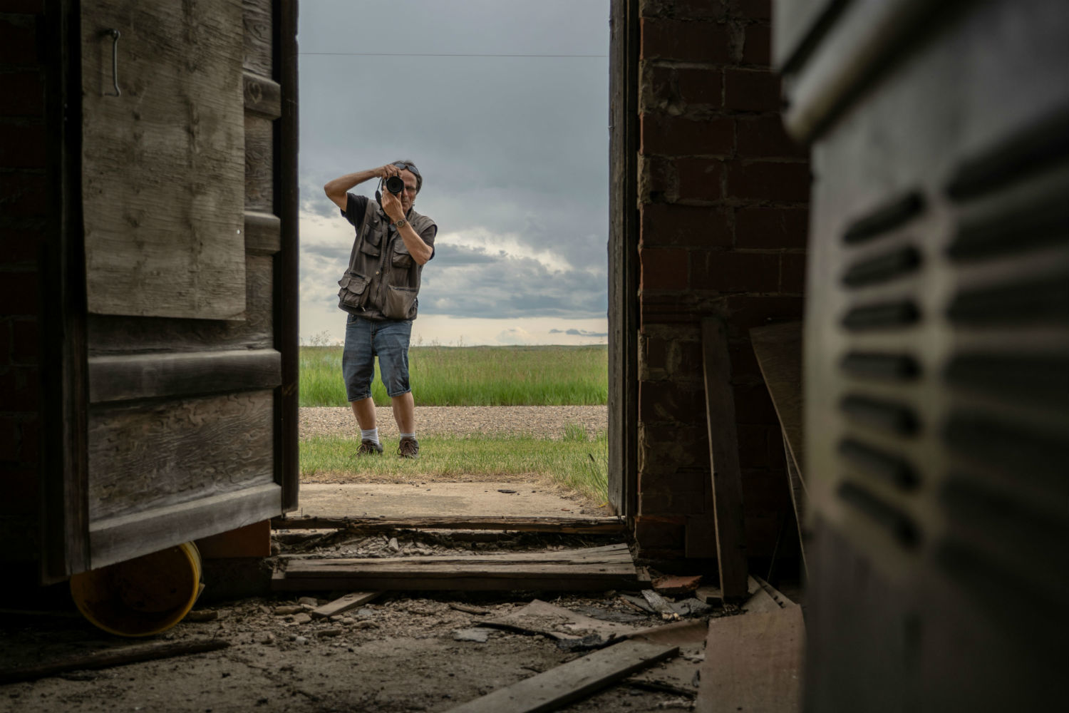 Johnnie Bachusky photographs a building through a doorway in Nemiskam, Alta. (Vincent Bonnay/Radio-Canada)