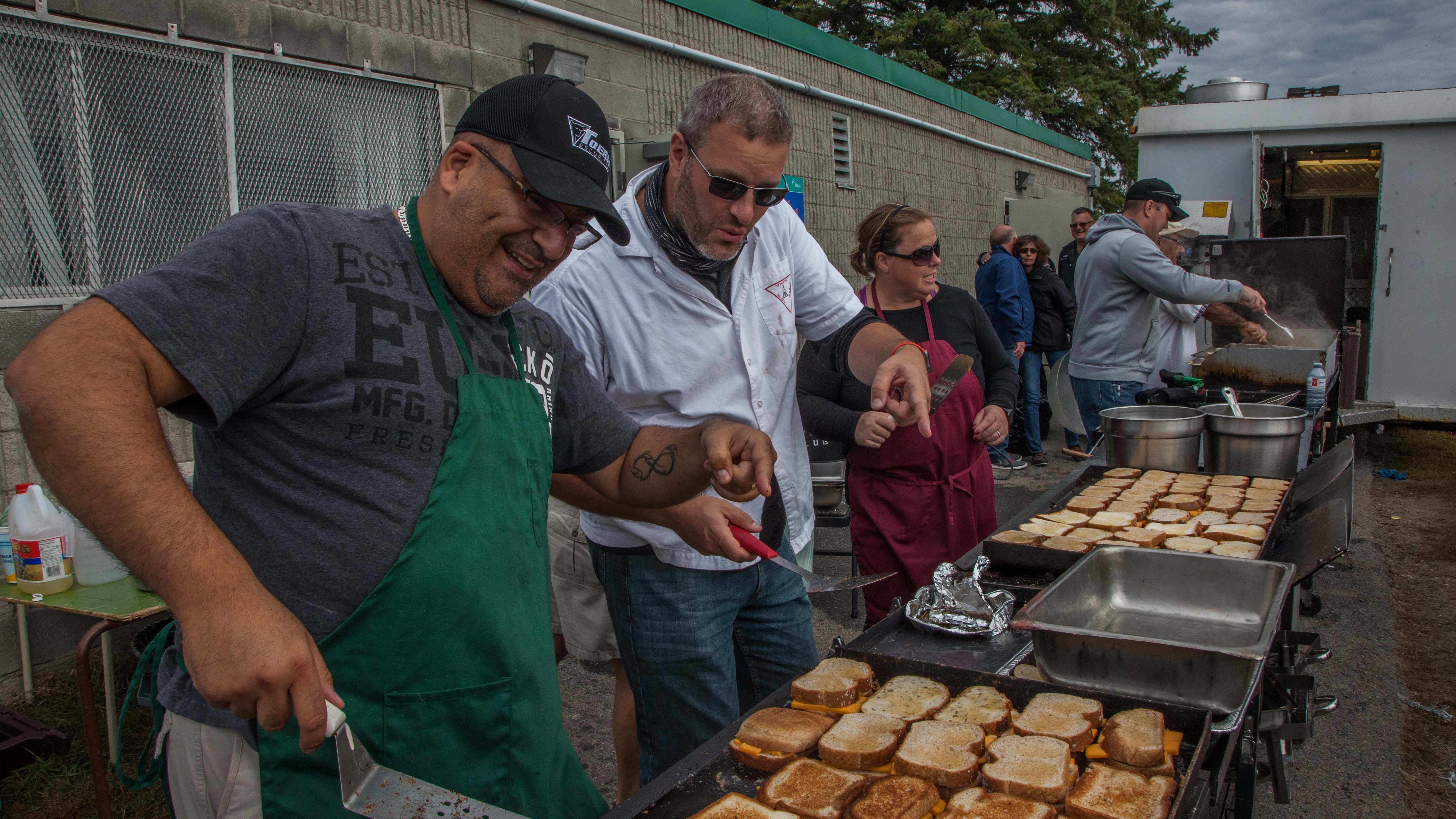 Volunteers make and hand out grilled cheese sandwiches in the Ottawa suburb of Barrhaven, where thousands were left without power the weekend after the storms. (Patrick Sauvé/Radio-Canada)