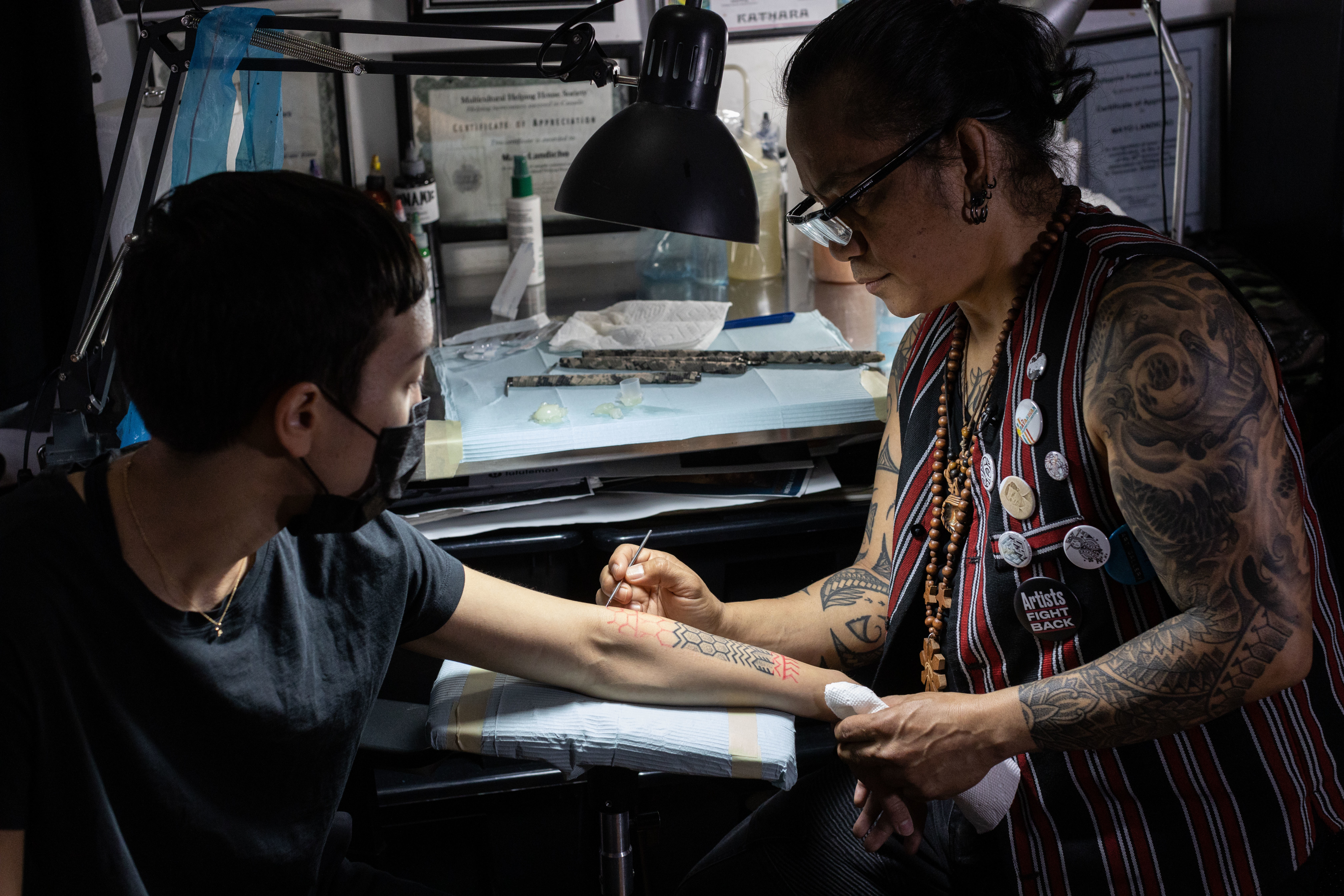 Mayo Landicho, right, sketches out a batok pattern on Jen Angelucci's forearm. (Gian-Paolo Mendoza/CBC)