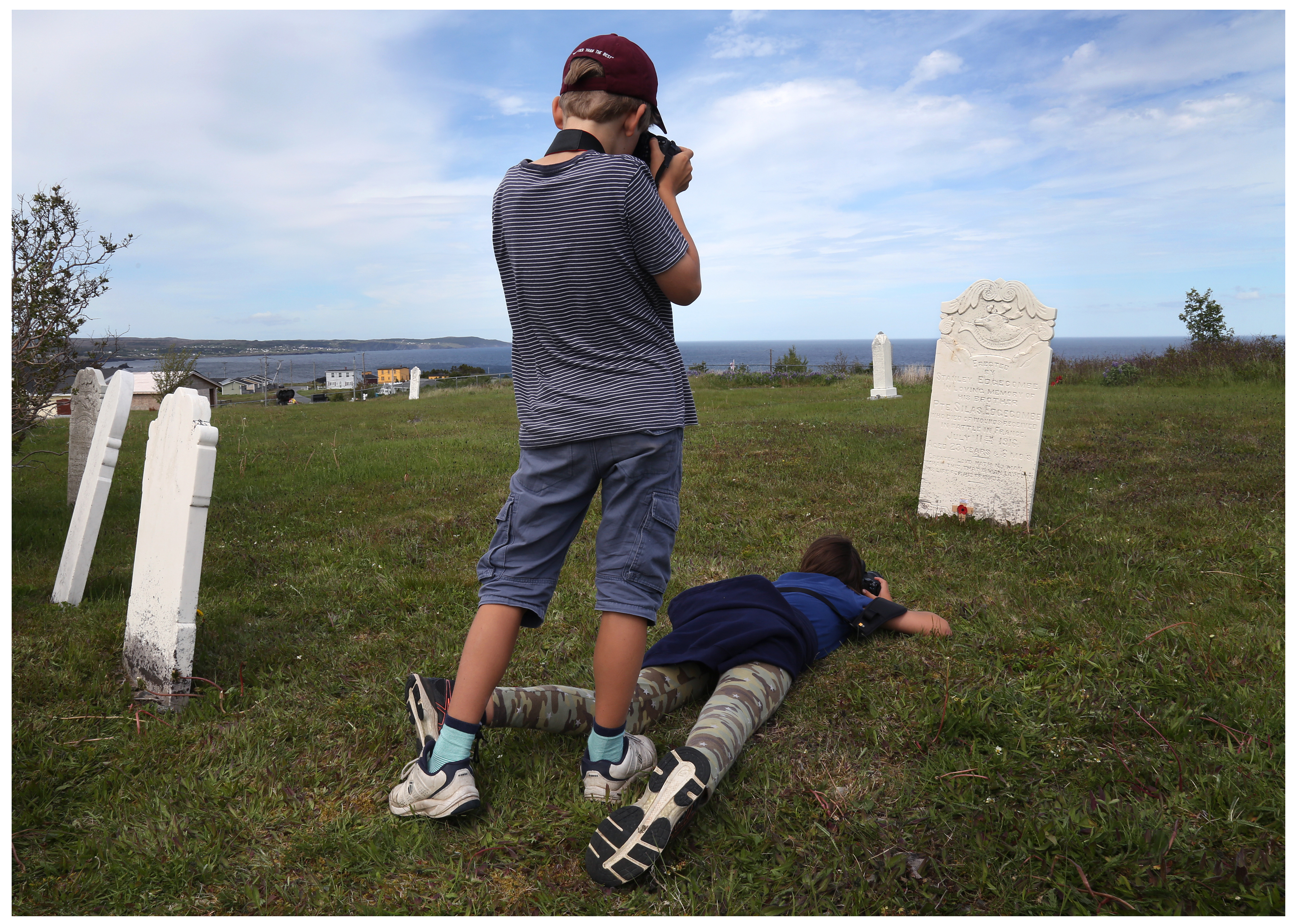 Students Oscar Heard, standing, and Zoe Spenceley, photograph the memorial marker for Silas Edgecombe, which his brother built at Ochre Pit Cove. (Paul Daly for CBC)