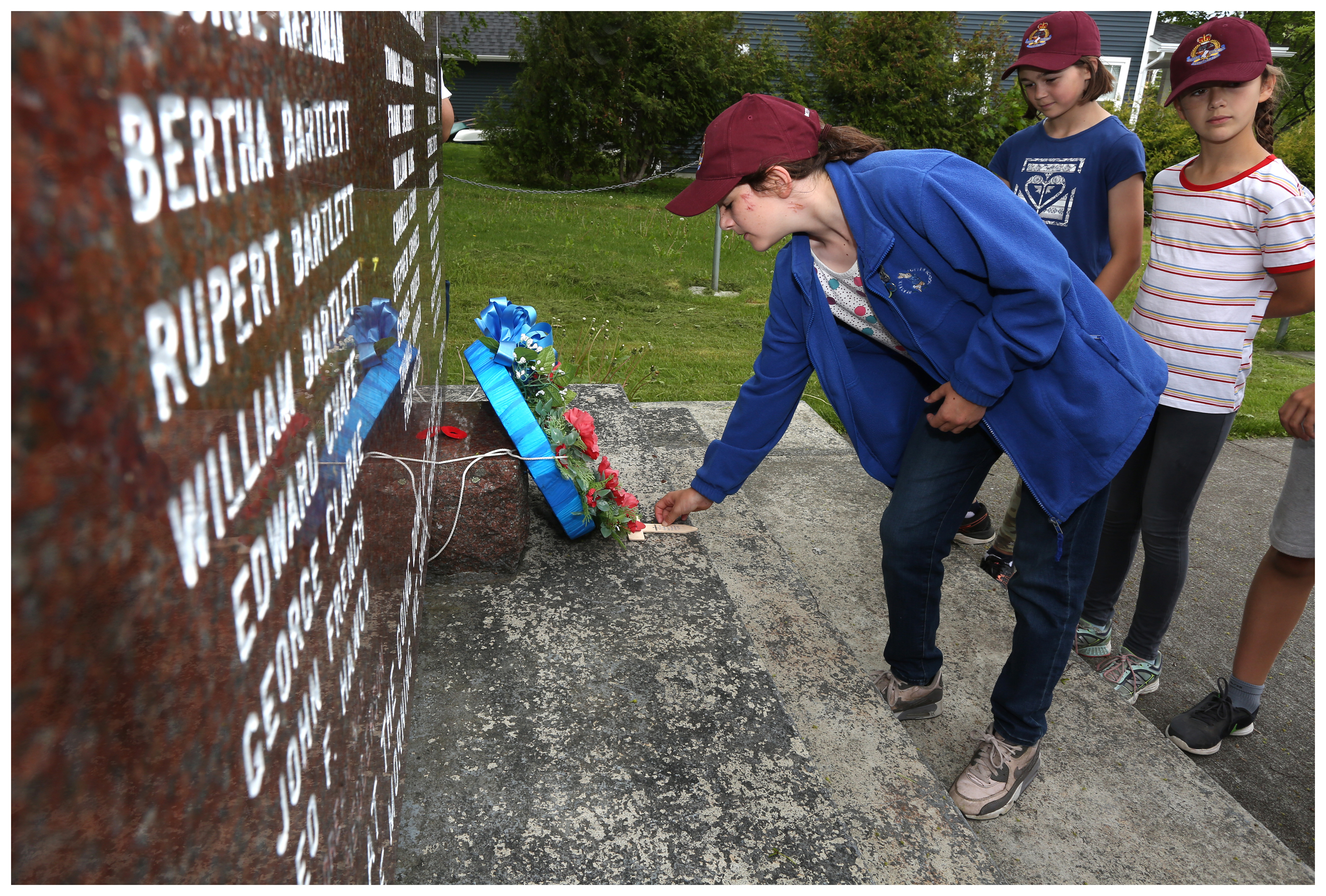 Alice Goldberger, observed by Zoe Spenceley (left) and Sophia Anderson, leaves a cross they made for nurse Bertha Barrett at the War Memorial in Bartlett's hometown of Brigus. (Paul Daly for CBC)