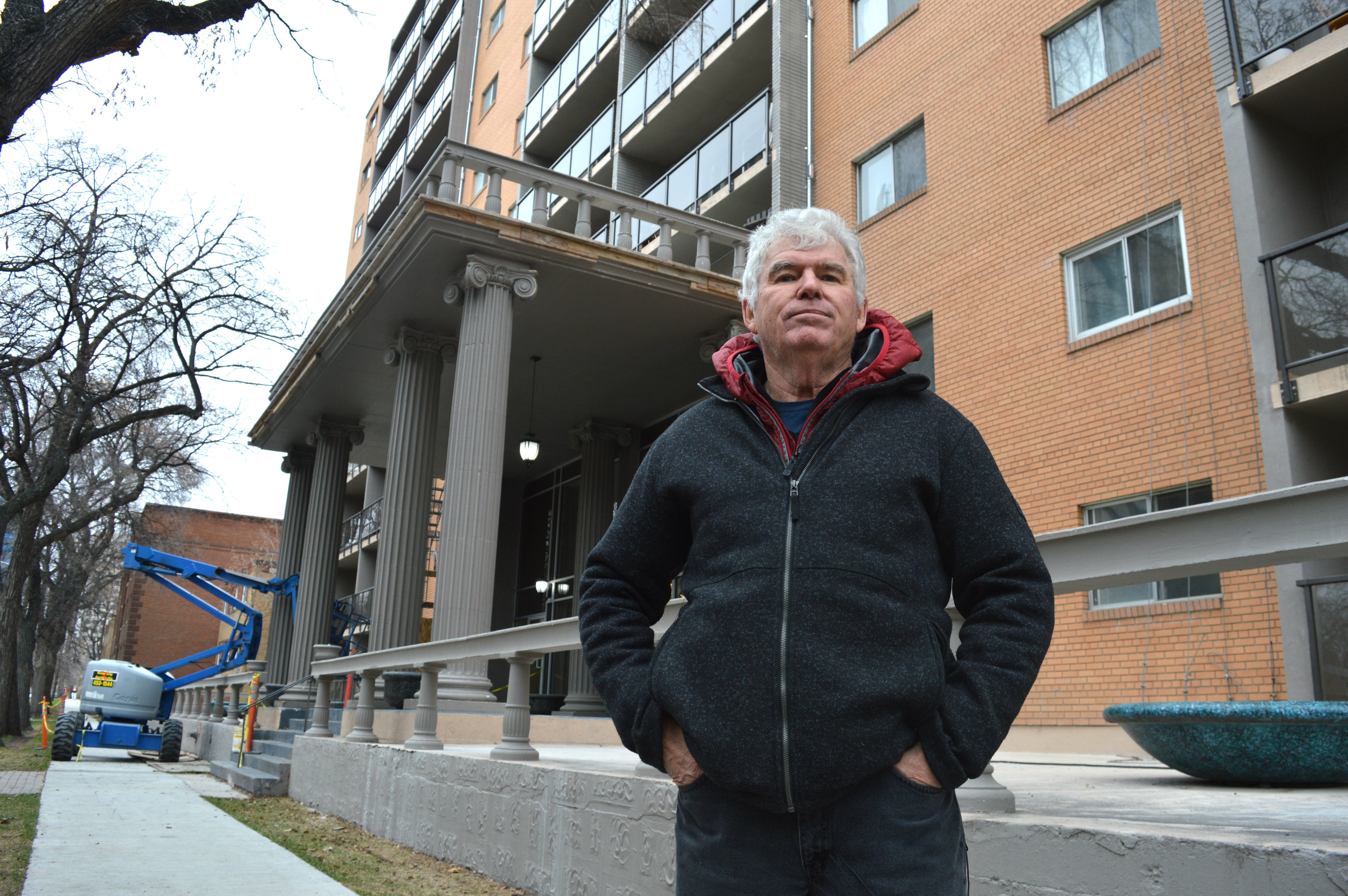 Bob Kelly, great-great-nephew of Thomas Kelly, stands in front of the Kelly House Apartments at the corner of Carlton Street and Assiniboine Avenue. (Cameron MacLean/CBC)