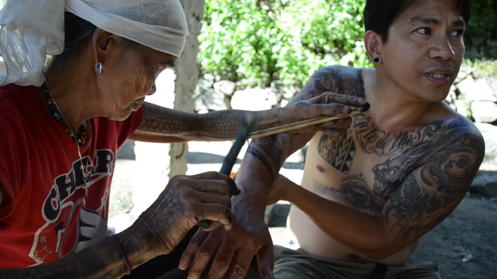 Mayo Landicho, right, receiving batok from Apo Whang-Od in the artist's village in the Kalinga province of the Philippines.