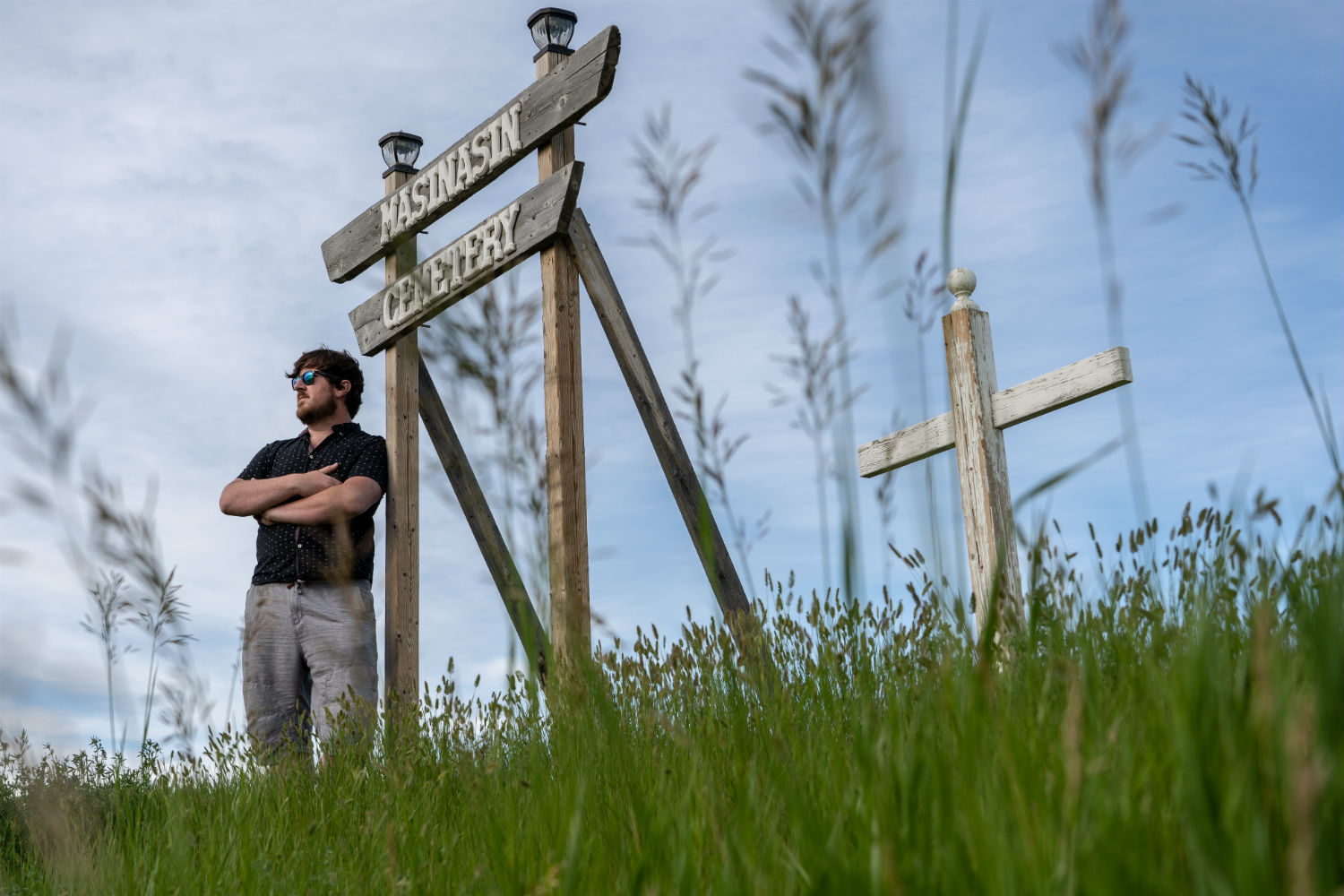 Cody Kapscos stands by a new sign for the old Masinasin Cemetery in southern Alberta. He took it upon himself to restore the small graveyard after coming across long-forgotten headstones in a field. (Vincent Bonnay/Radio-Canada)