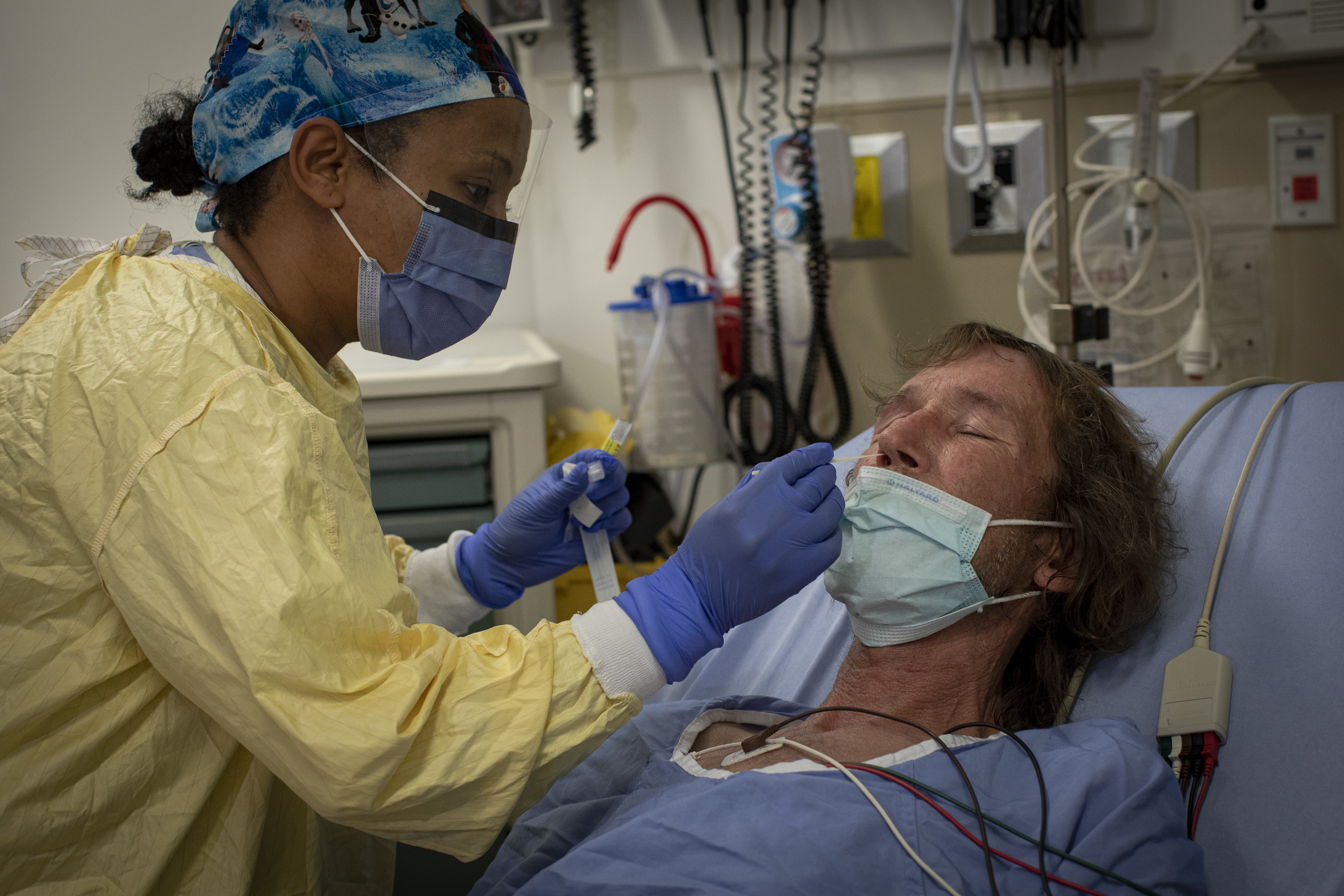 A health-care worker administers a COVID-19 swab test on 56-year-old Rick Furchner, who's in the Scarborough General emergency department because of pain caused by a blood clot. (Evan Mitsui/CBC)