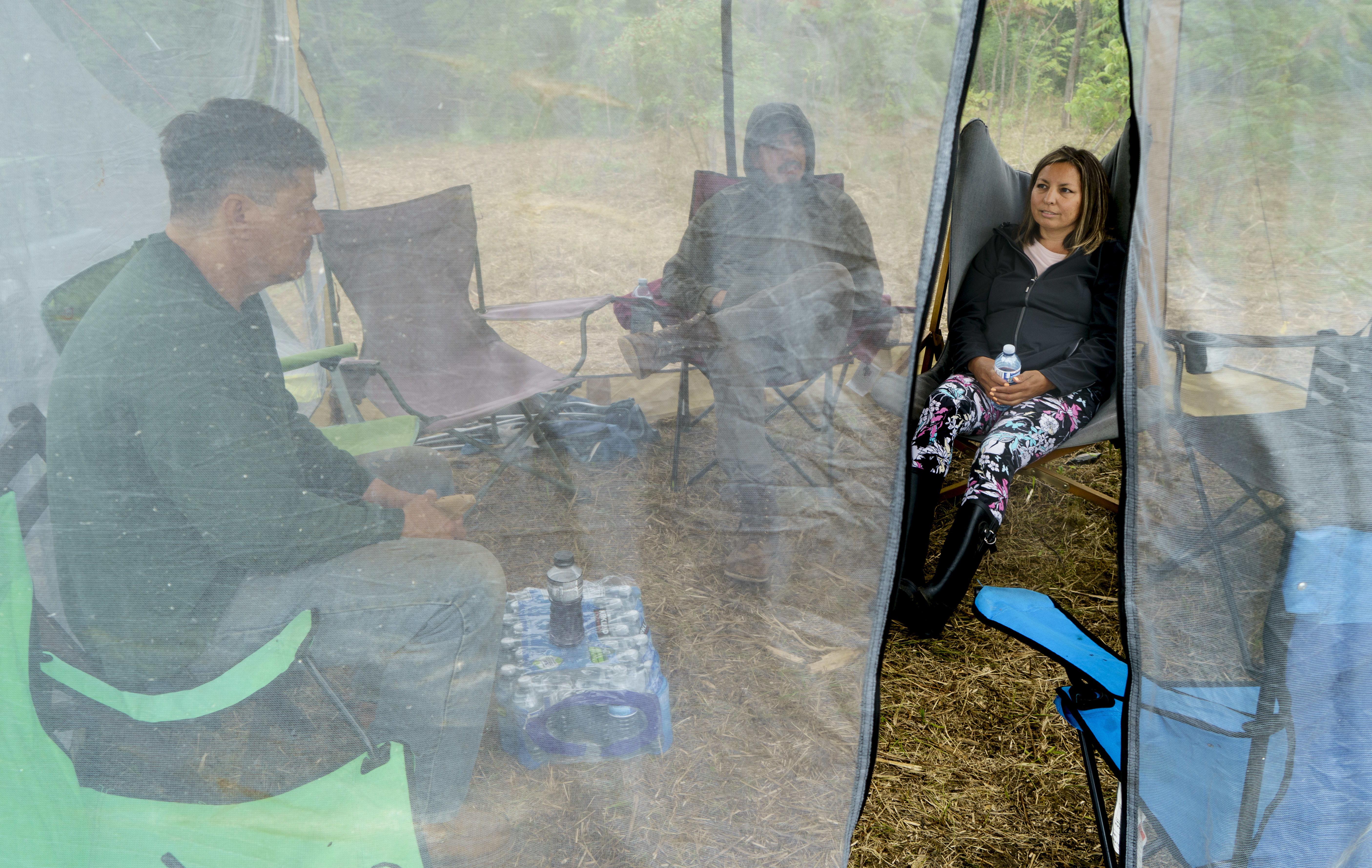 Karihwakatste Deer sits in a tent with fellow community members in a camp in Kahnawake on July 8. (Paul Chiasson/Canadian Press)