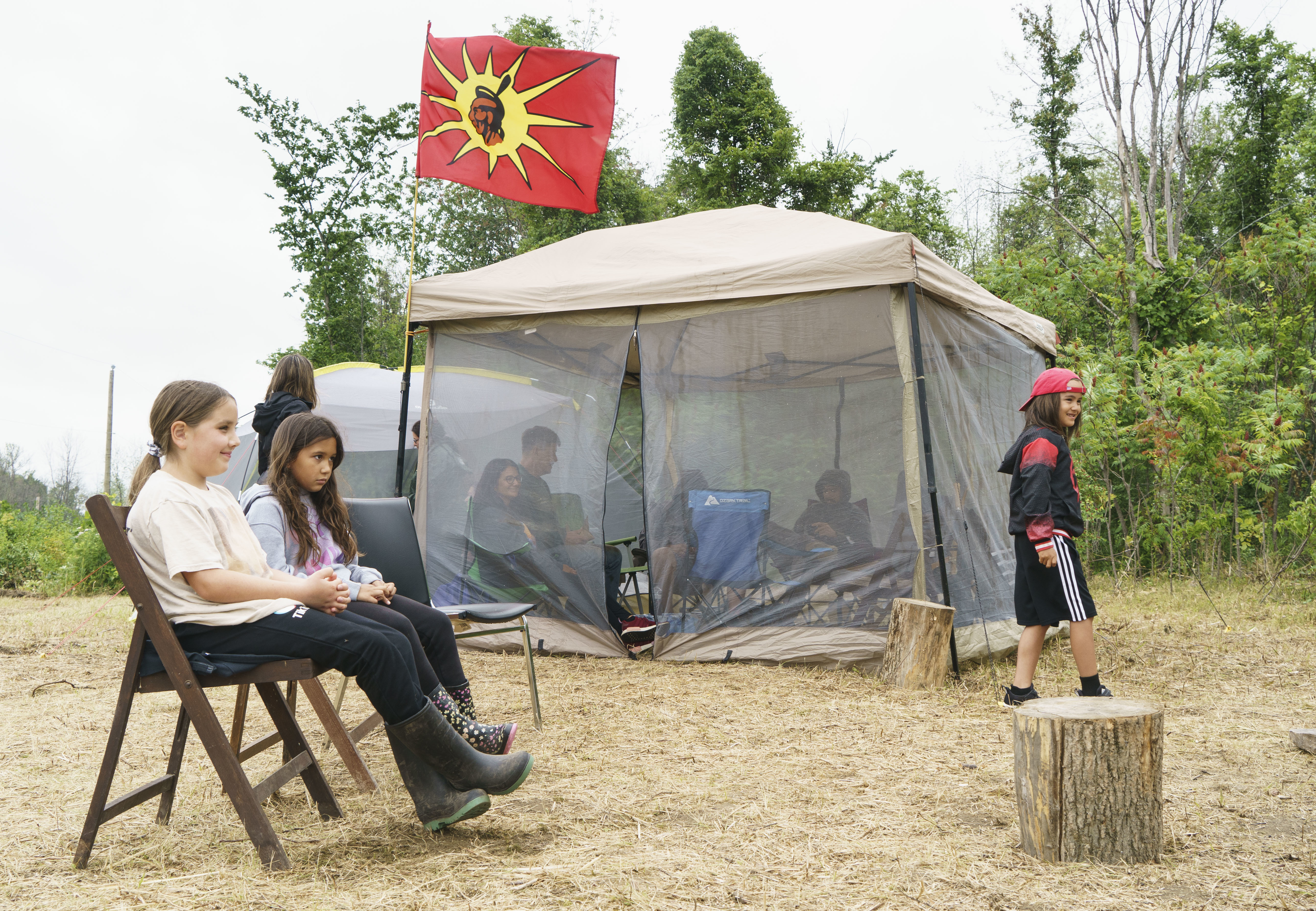 Children sit in a camp in Kahnawake next to where community members are occupying a disputed parcel of land to stop a proposed housing project on July 8. (Paul Chiasson/Canadian Press)