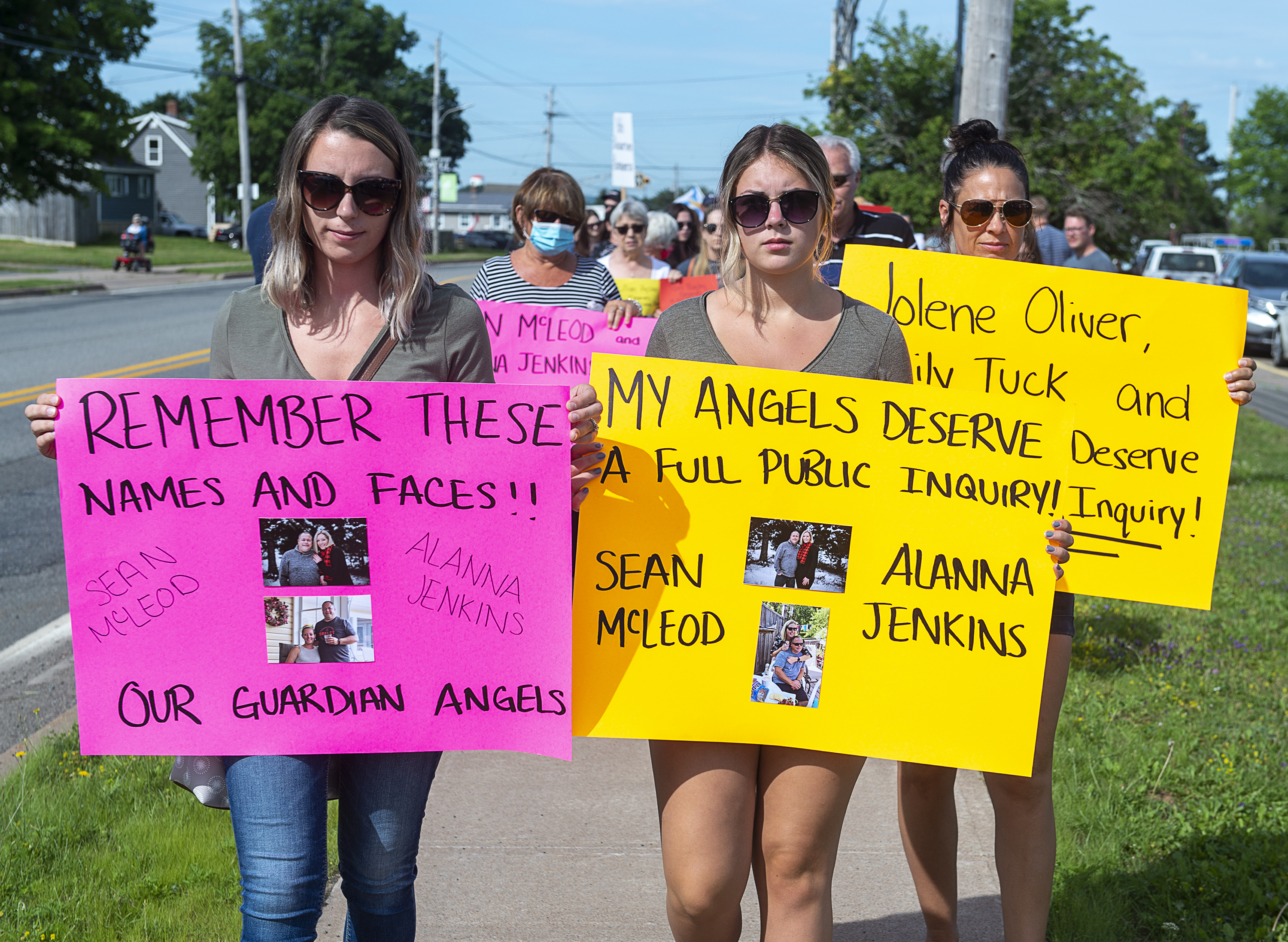 Family and friends of victims, including Sean McLeod's daughters, Taylor Andrews, left, and Amielia McLeod, attend a march demanding an inquiry into the April mass shooting in Nova Scotia that killed 22 people, in Bible Hill, N.S., on July 22, 2020. (Andrew Vaughan/The Canadian Press)