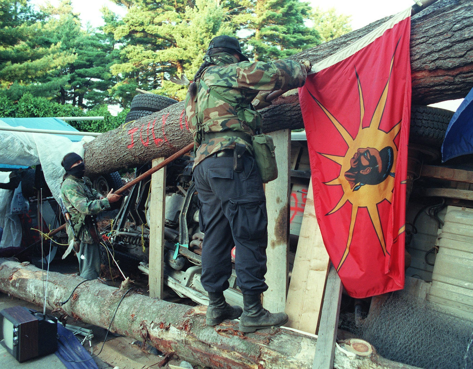 Two masked Mohawk Warriors remove a flag from the main barricade at Oka, Que., September 1, 1990, in order to keep it from falling into the hands of Canadian army. (Tom Hanson/The Canadian Press)