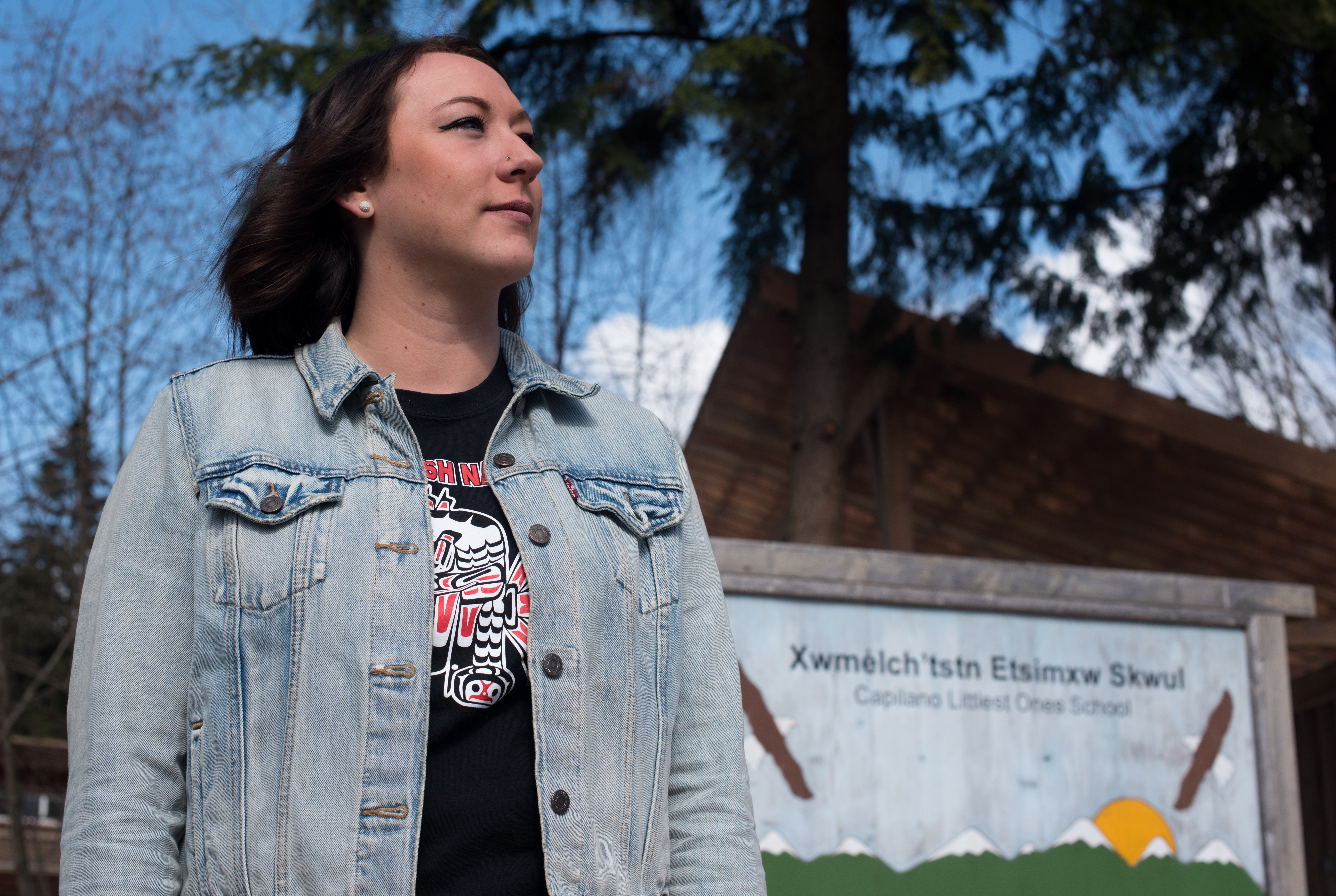 Carey McReynolds, a graduate of last year's Skwomesh immersion course at Simon Fraser University, stands in front of Capilano Littlest Ones School, where she currently works. (Dustin Patar/Marc Fawcett-Atkinson)
