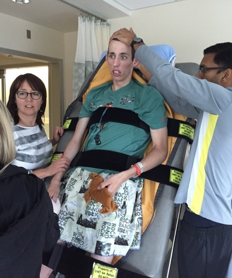 Chase is lifted upright for the first time since his coma. (Submitted by Pamela Davis)
