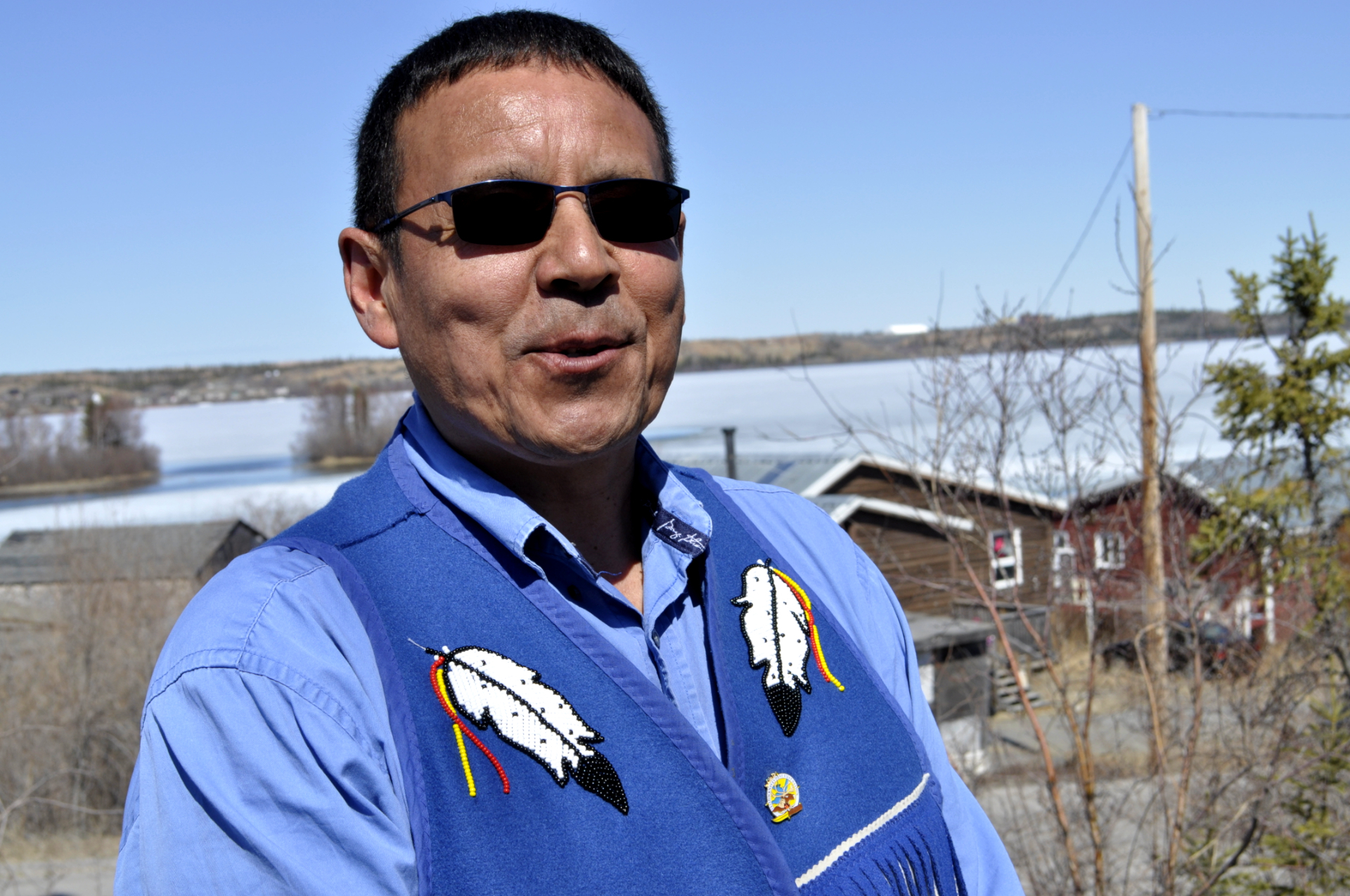 Yellowknives Dene Chief Ernest Betsina in Ndilo, N.W.T. Behind him is Giant Mine, a visible reminder of the worst-case scenario when a mining company collapses. (Alex Brockman/CBC)