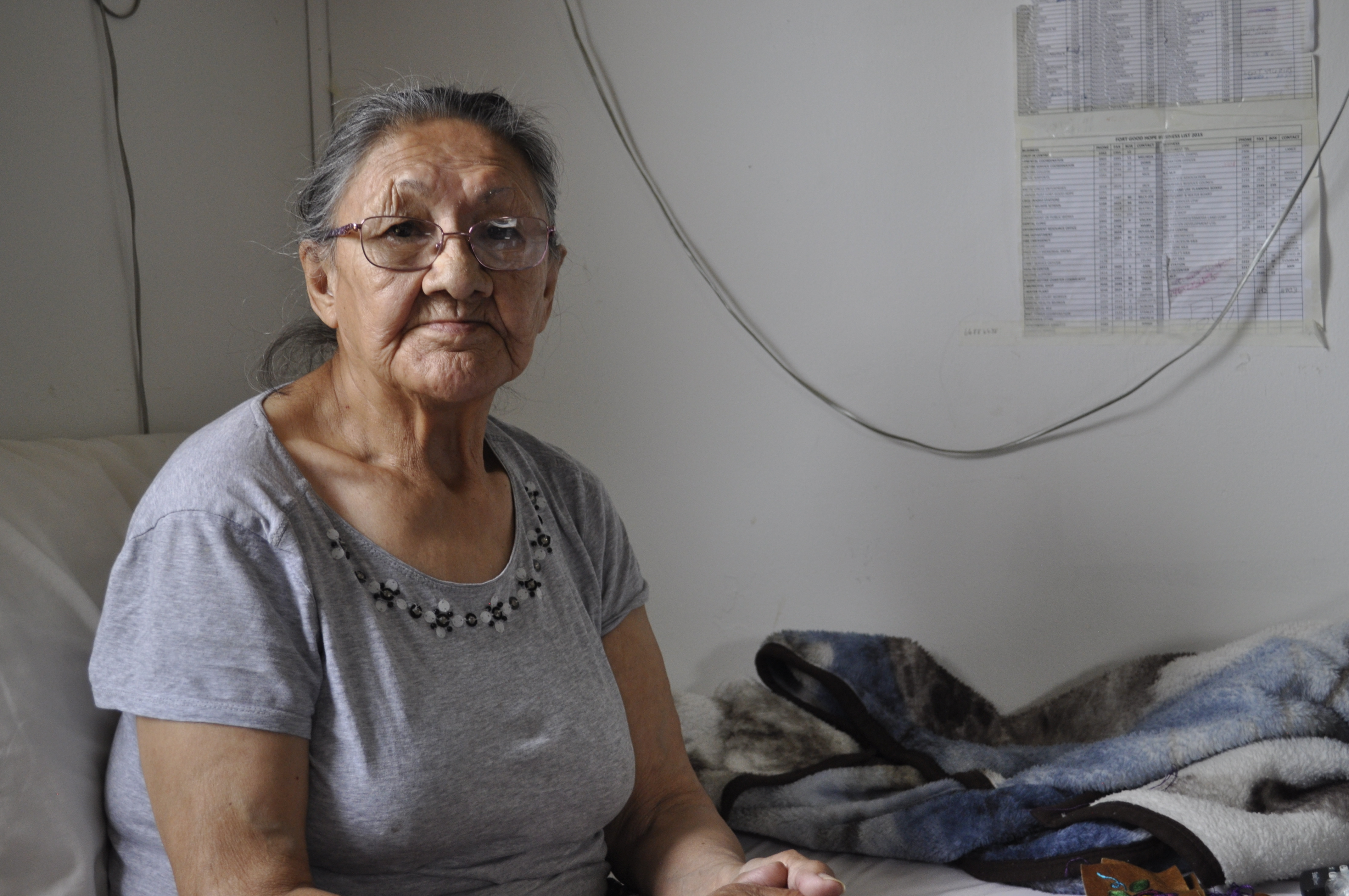 Margaret Kelly sits in her home in Fort Good Hope, N.W.T. She's done fighting the land and is ready to move out. (Alex Brockman/CBC)